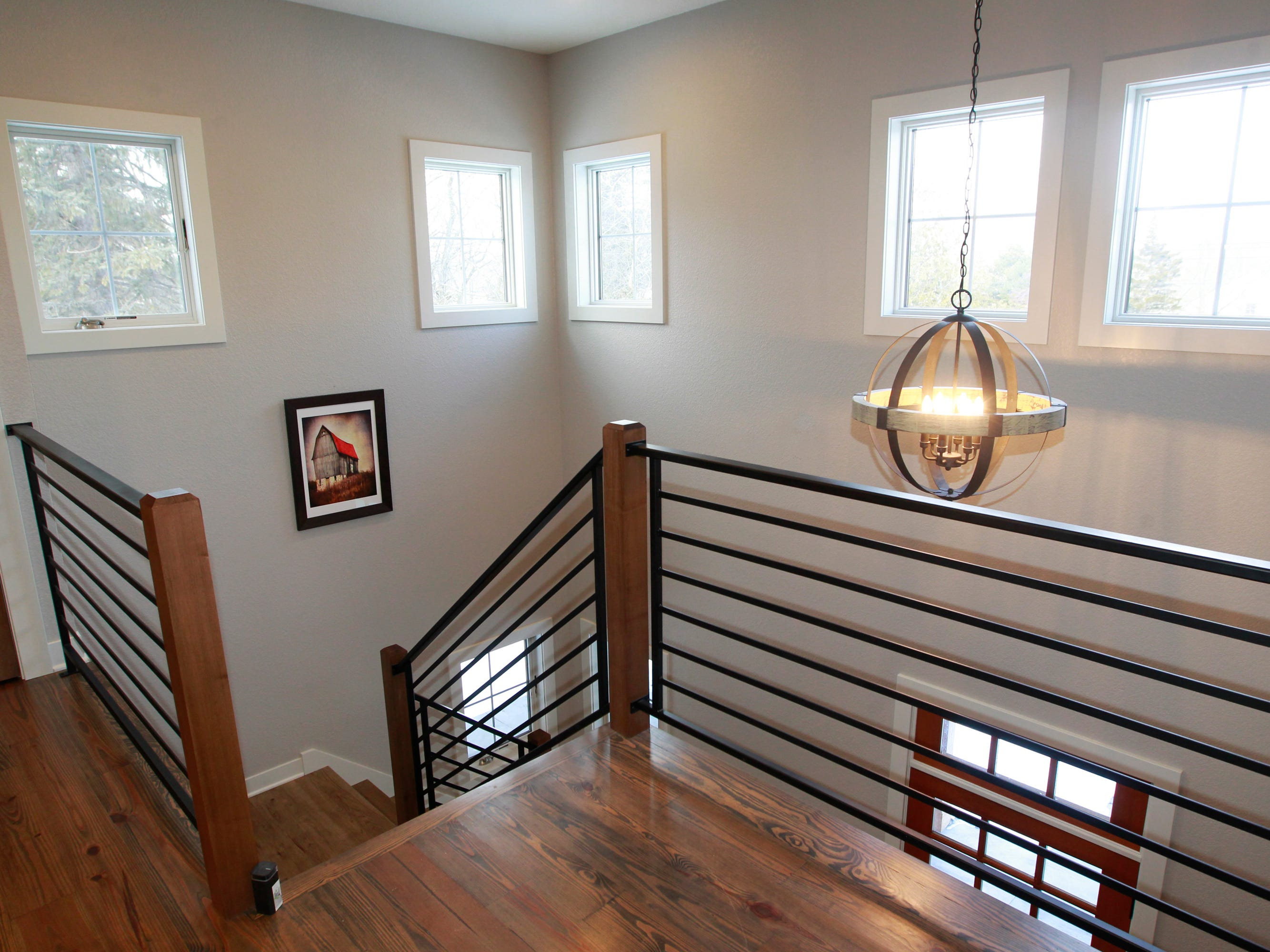 Custom-made metal railings are a modern accent in the farmhouse design of the home.