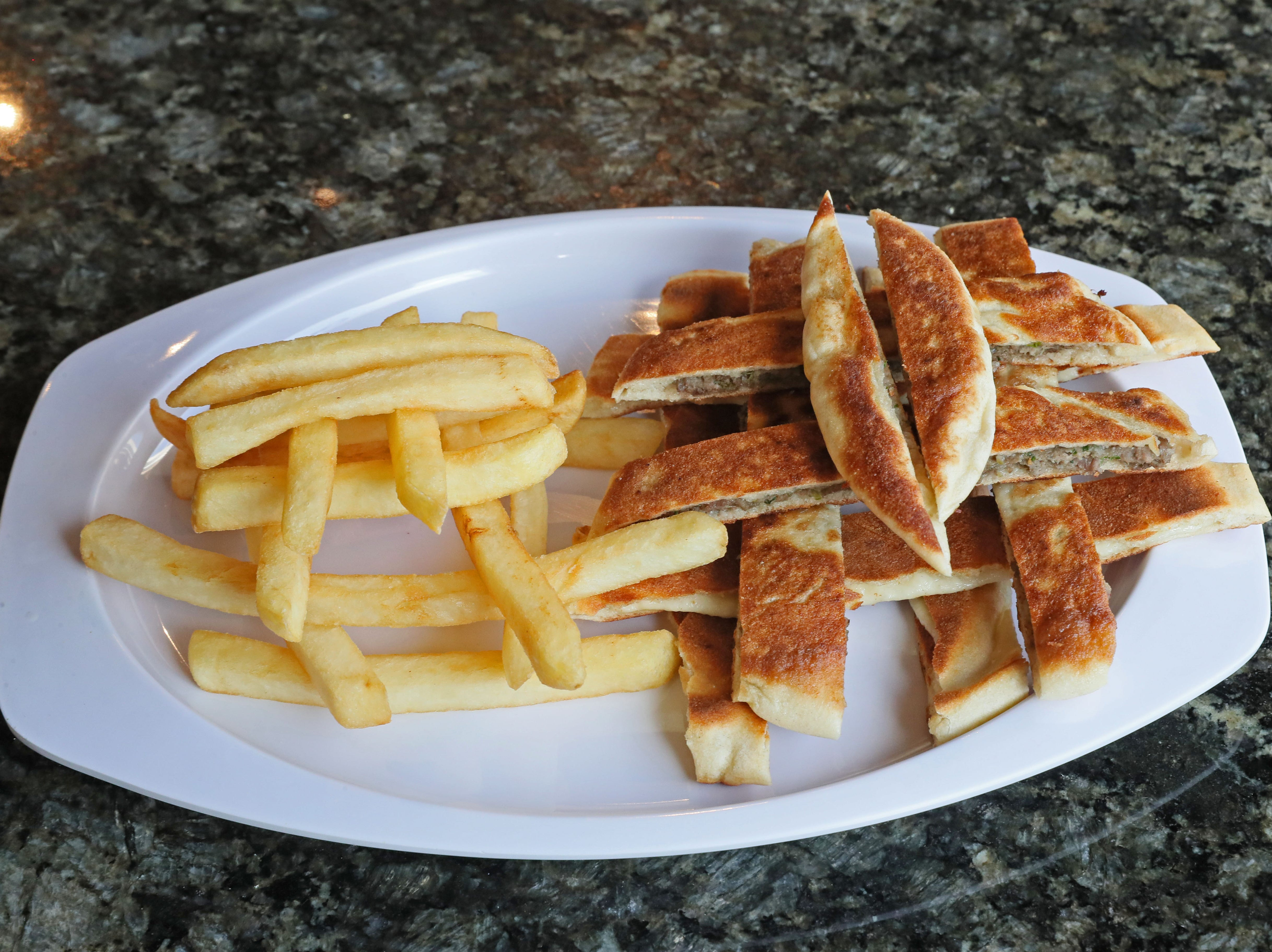 Arayes, pita that's stuffed with beef or cheese and baked, is served whole for adults; here it's shown sliced and served with fries for Pita Palace's children's menu.