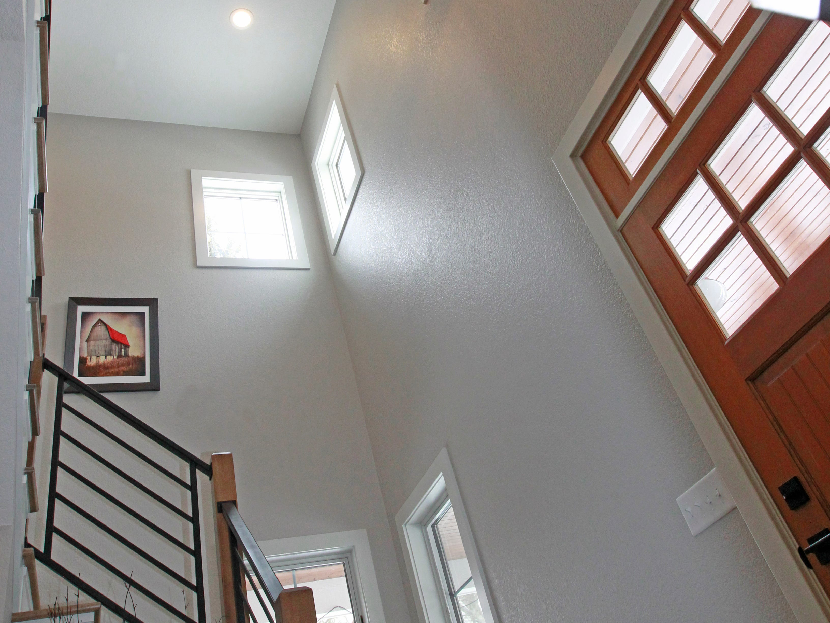 The staircase adds a decidedly modern touch to the farmhouse design.