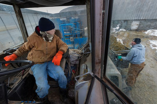 Isaac Crosby, 12, engages the feed mixer while his father, Tom Crosby, waits to give him the signal to stop on his family's farm in Shell Lake. Tom Crosby, a fourth-generation farmer, partners with his brother, Garry, milking 110 cows. They also raise heifers and  beef cattle.