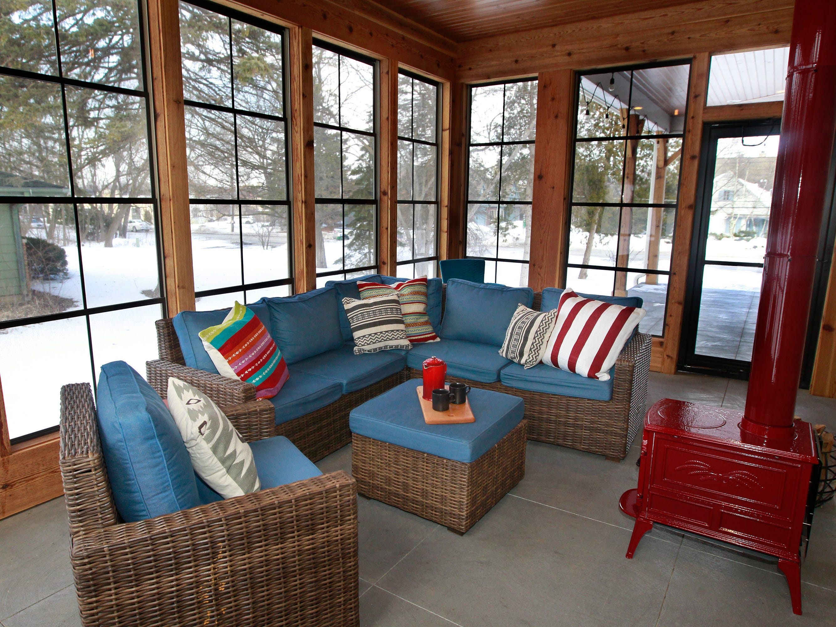 A three-season room is a favorite spot for family and friends to gather. It features cedar wood and floor-to-ceiling windows and a red wood-burning stove.
