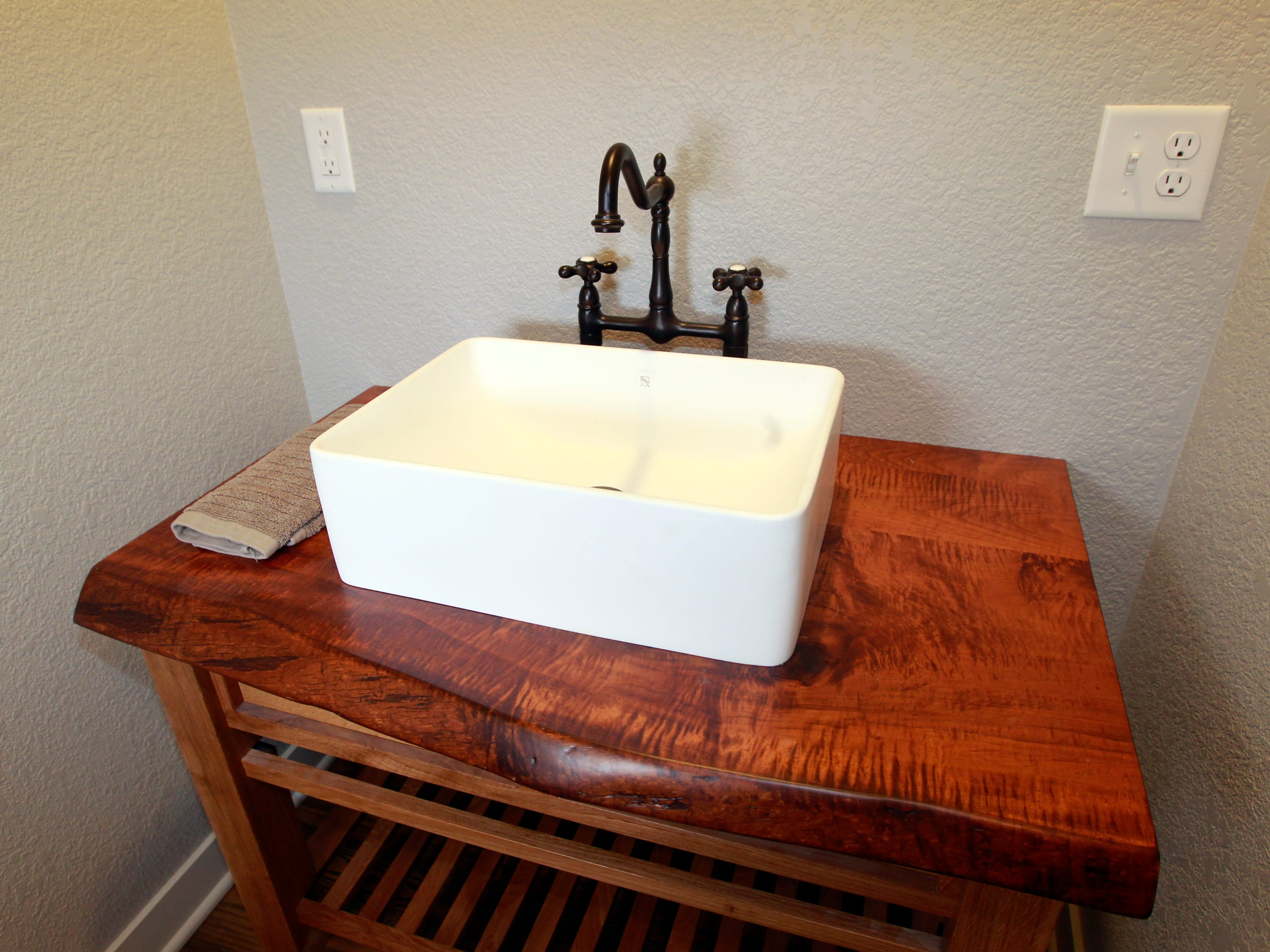 A curly maple live-edge top with a white vessel sink and brass fixtures is in the laundry room.