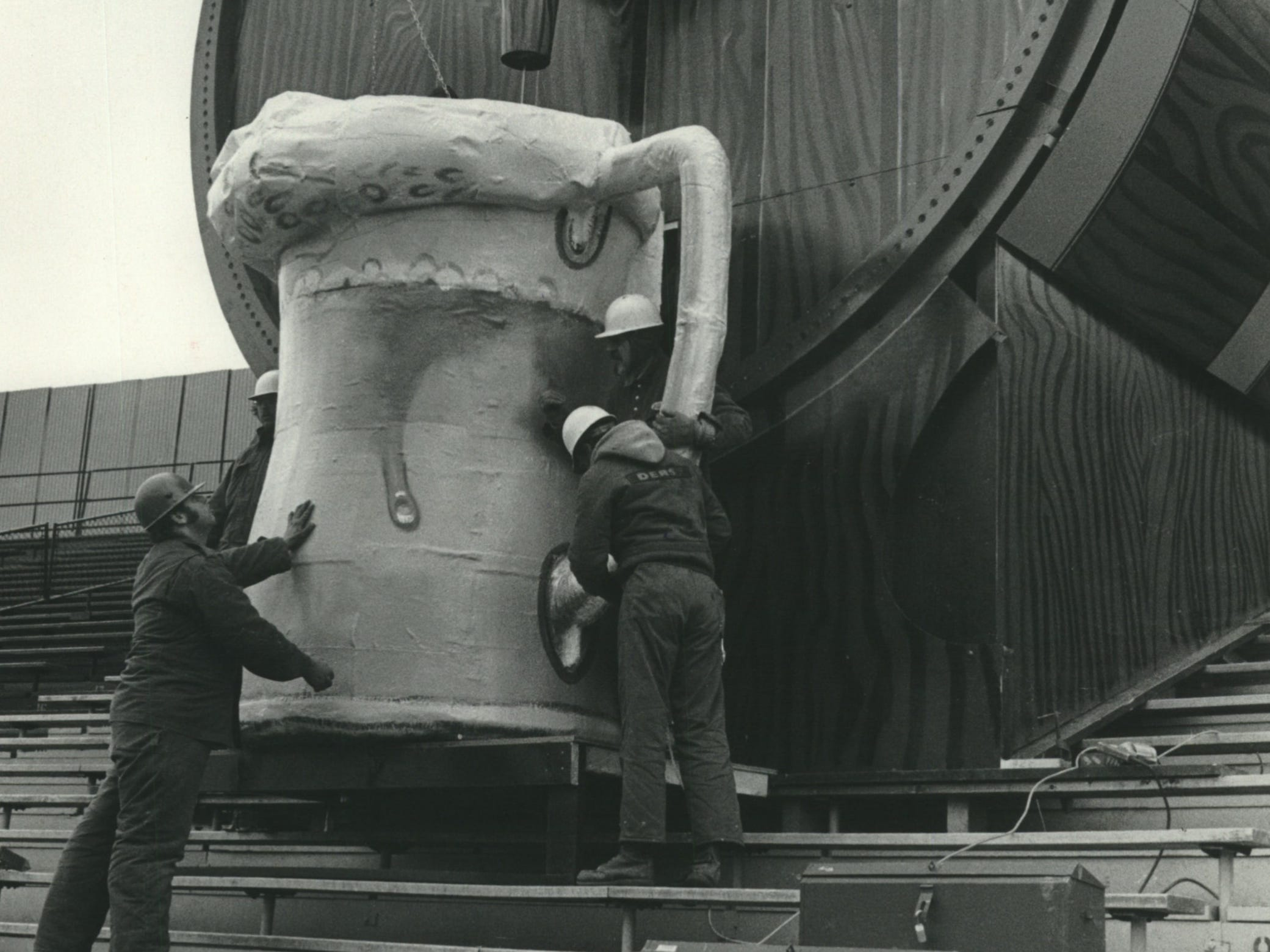 """Workers install the mug under the giant beer barrel built in the center field bleachers at Milwaukee's County Stadium in early April 1973. On top of the barrel was a tiny chalet housing Brewers mascot Bernie Brewer, """"played"""" by a man in lederhosen and a Bavarian-style cap."""