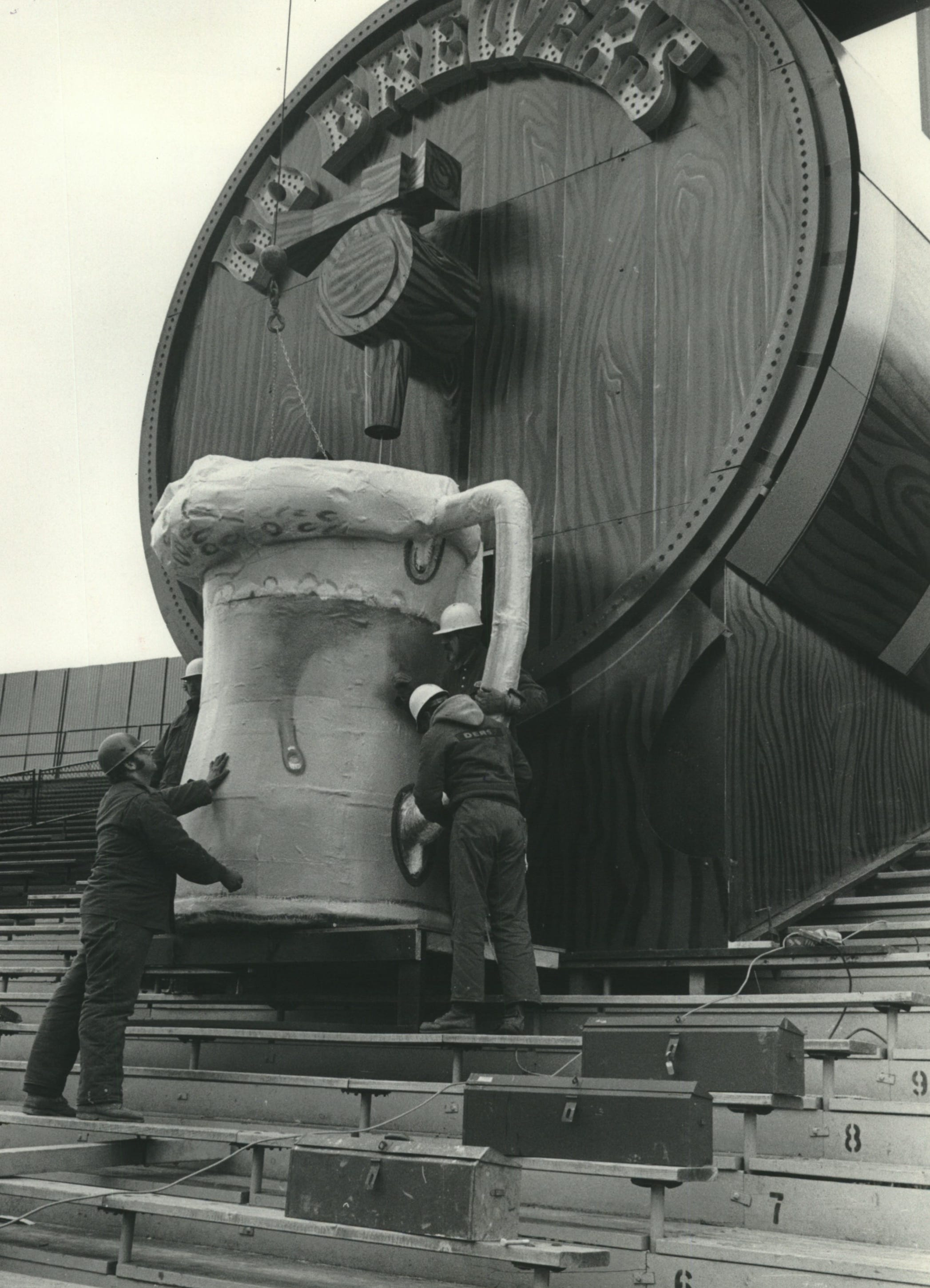 "Workers install the mug under the giant beer barrel built in the center field bleachers at Milwaukee's County Stadium in early April 1973. On top of the barrel was a tiny chalet housing Brewers mascot Bernie Brewer, ""played"" by a man in lederhosen and a Bavarian-style cap."