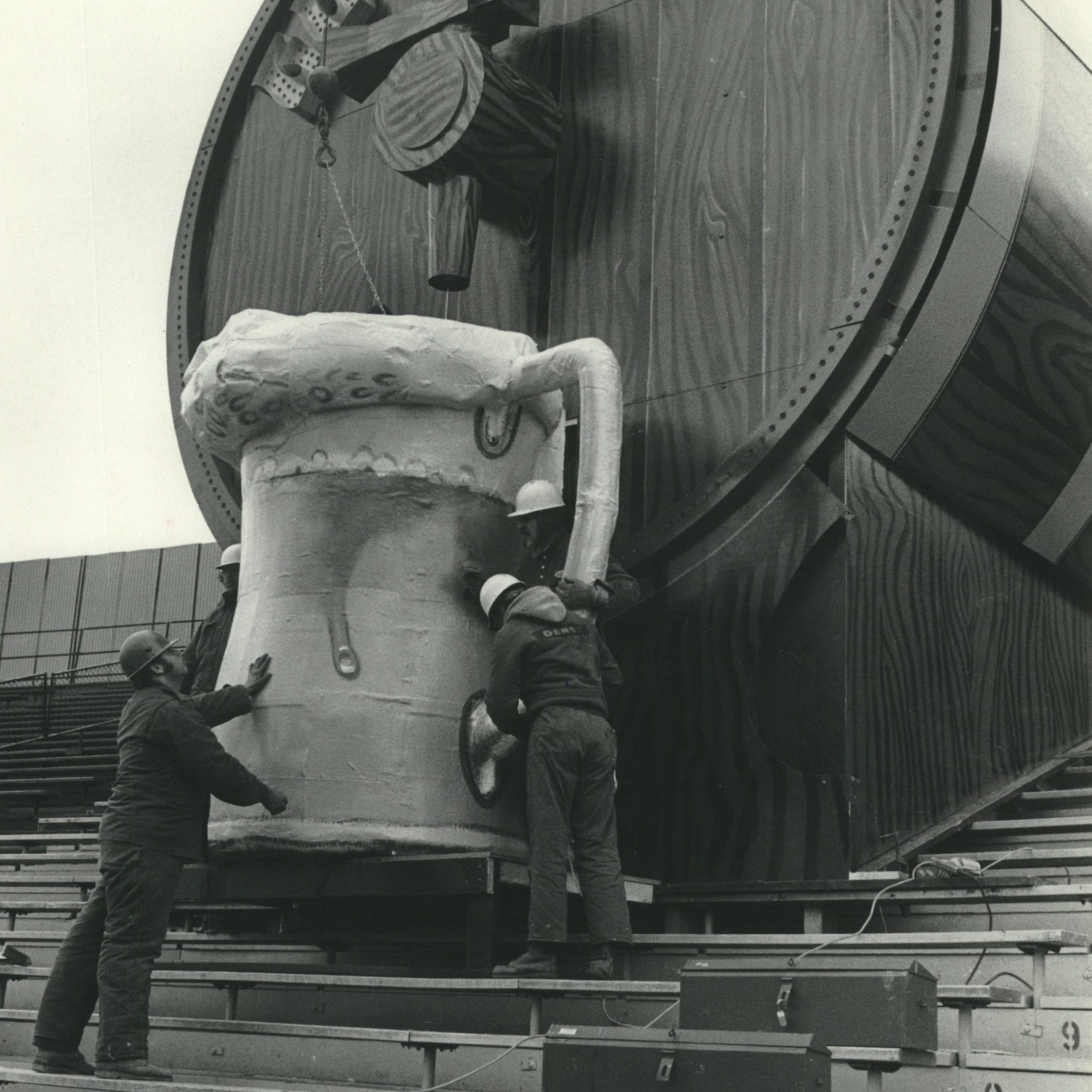 Workers install the mug under the giant beer...