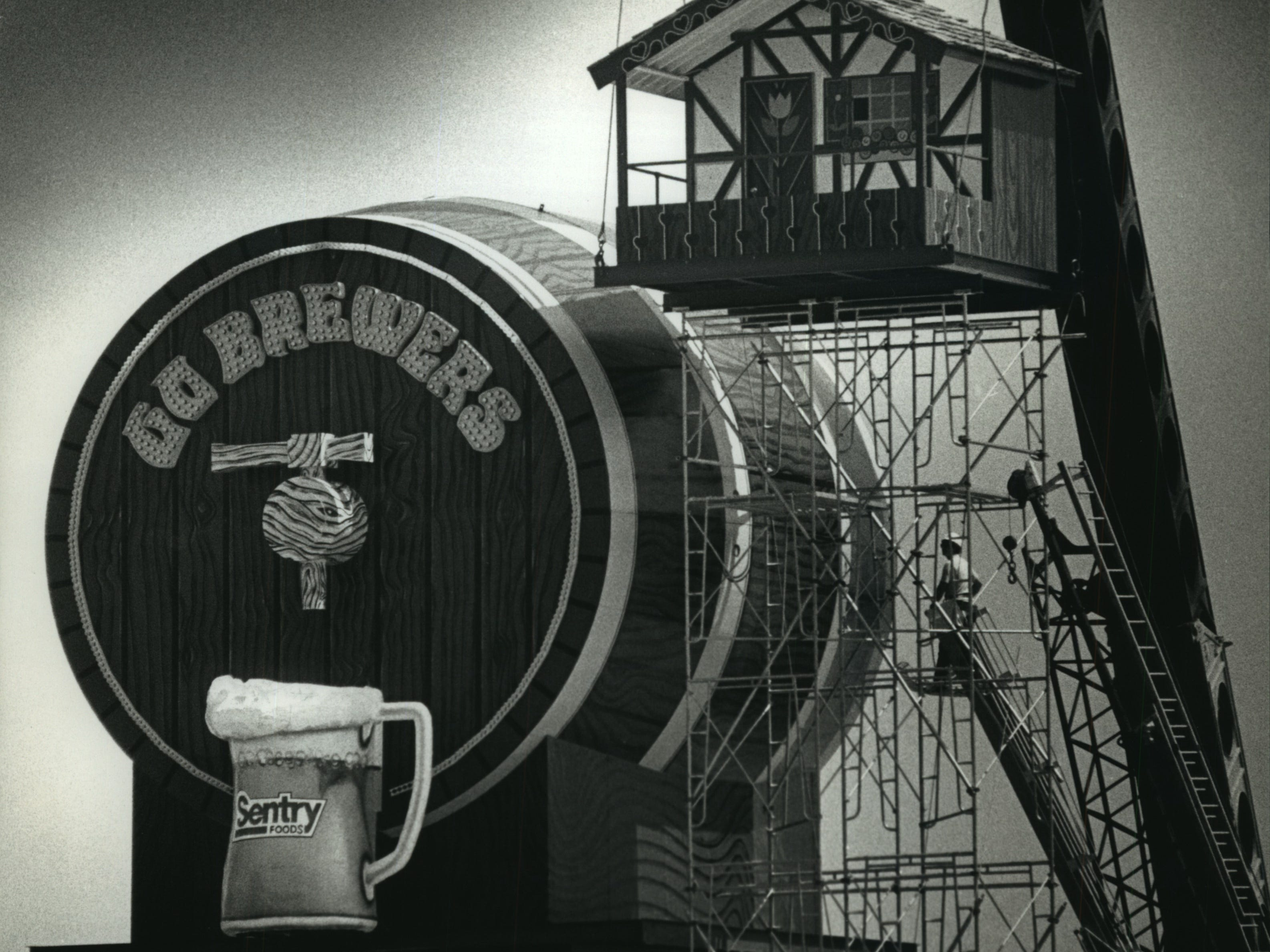 Workers complete the reinstallation of Bernie Brewer's chalet and accompanying beer keg and mug, at Milwaukee County Stadium on May 26, 1993. A crew from Derse Inc. of Milwaukee placed the chalet next to the beer barrel beyond the centerfield bleachers. The chalet, which features the Brewers' mascot descending on a slide from the chalet into the mug when the Brewers hit a home run, first appeared at the stadium in 1973. It was removed in 1984 because the chalet blocked the center-field speaker of the stadium's then-new sound system.
