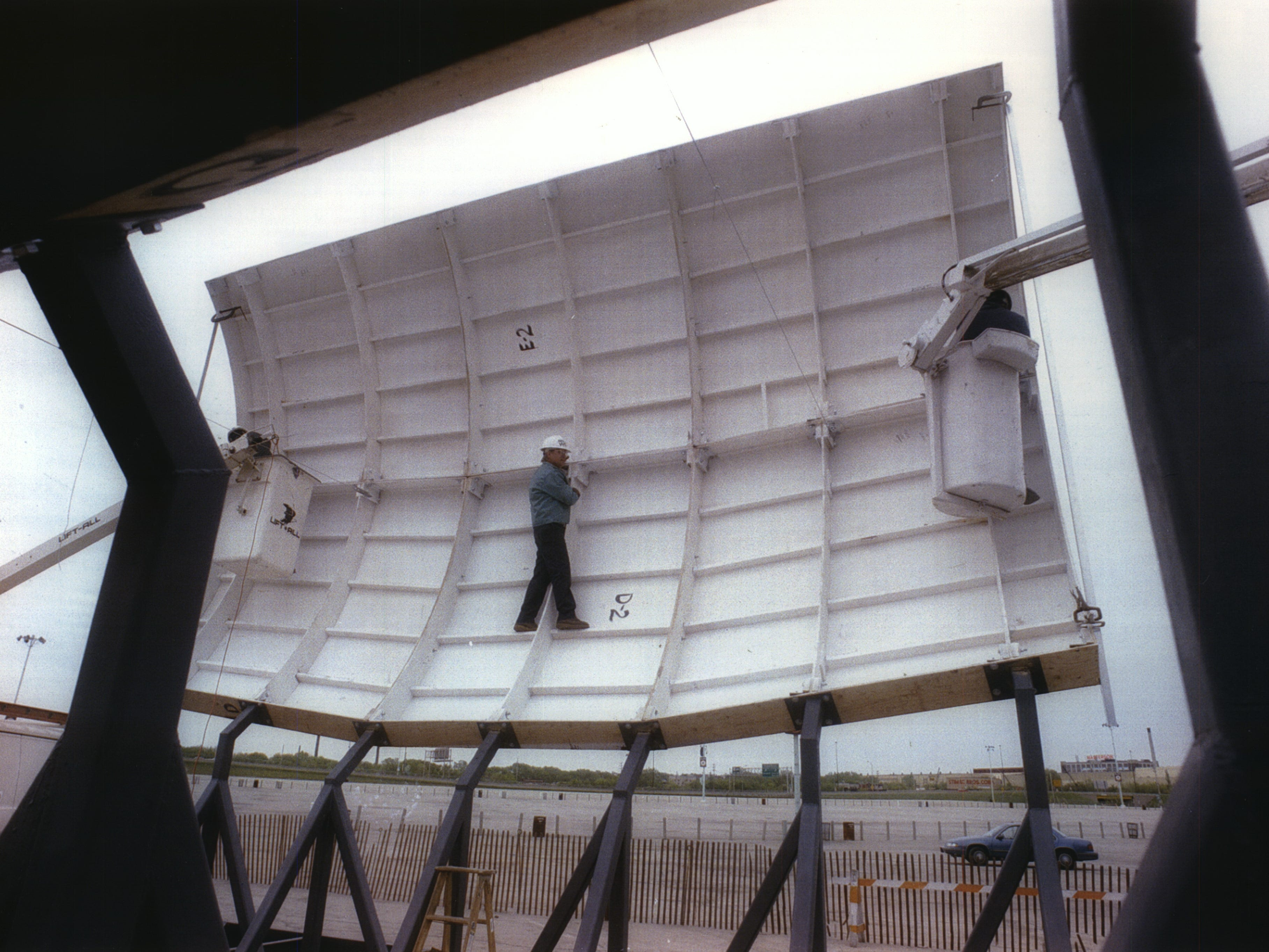 A worker is dwarfed by one of the steel sections making up the new beer barrel below Bernie Brewer's reconstituted chalet outside County Stadium on May 17, 1993. This photo was published in the May 18, 1993, Milwaukee Sentinel.