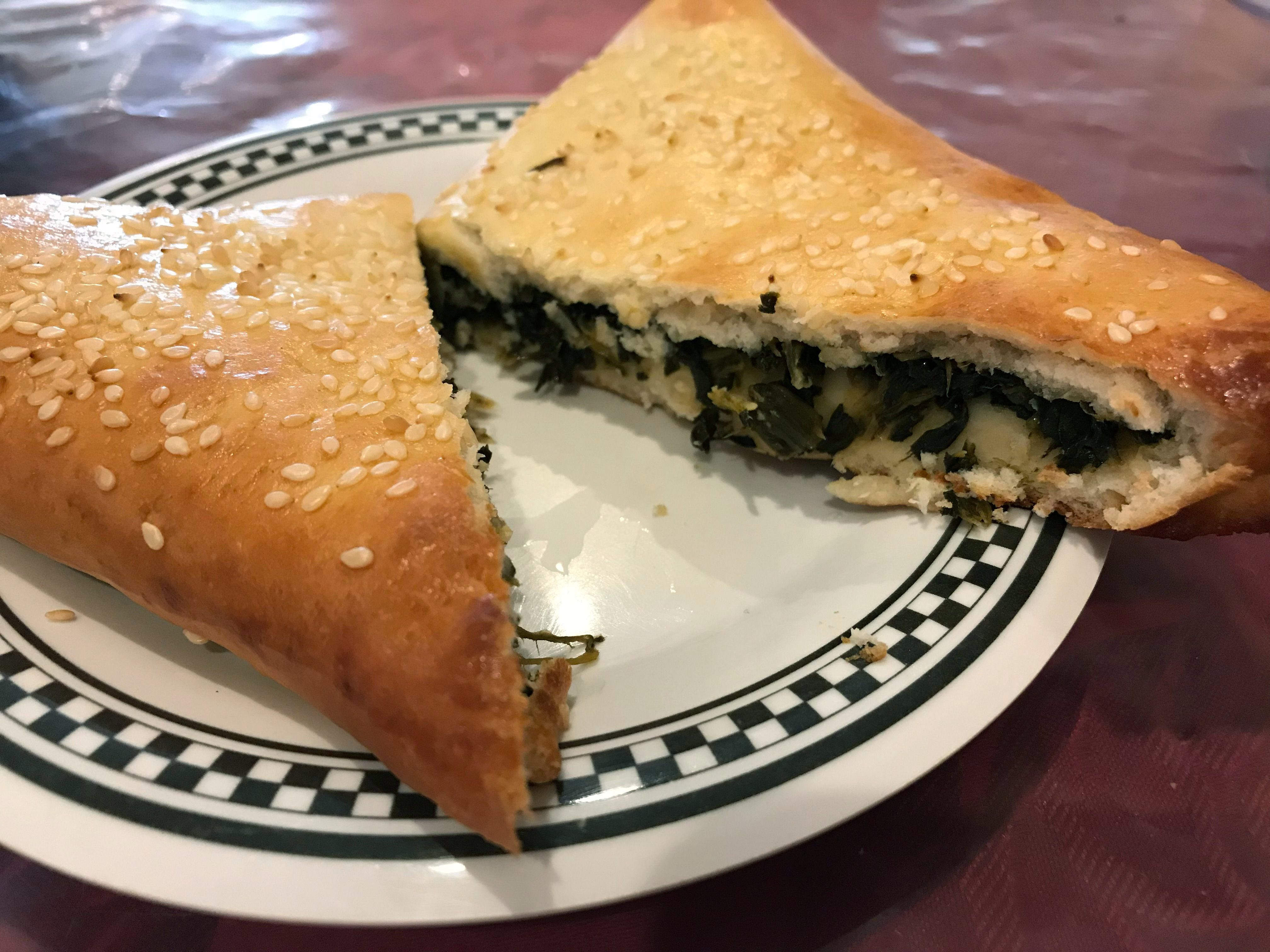 A large, triangular fatayer, a savory Syrian hand pie, is cut open to reveal the filling of lightly spicy fresh spinach at Damascus Gate, 807 W. Mitchell St.