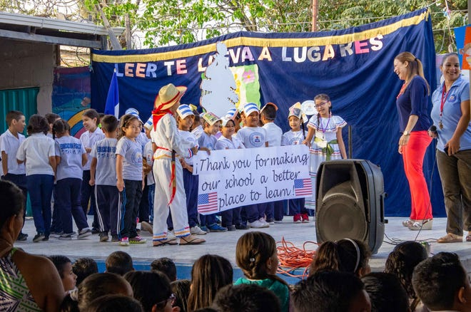 Children in Tegucigalpa, Honduras, celebrate the installation of a library as part of the Chispa Project.