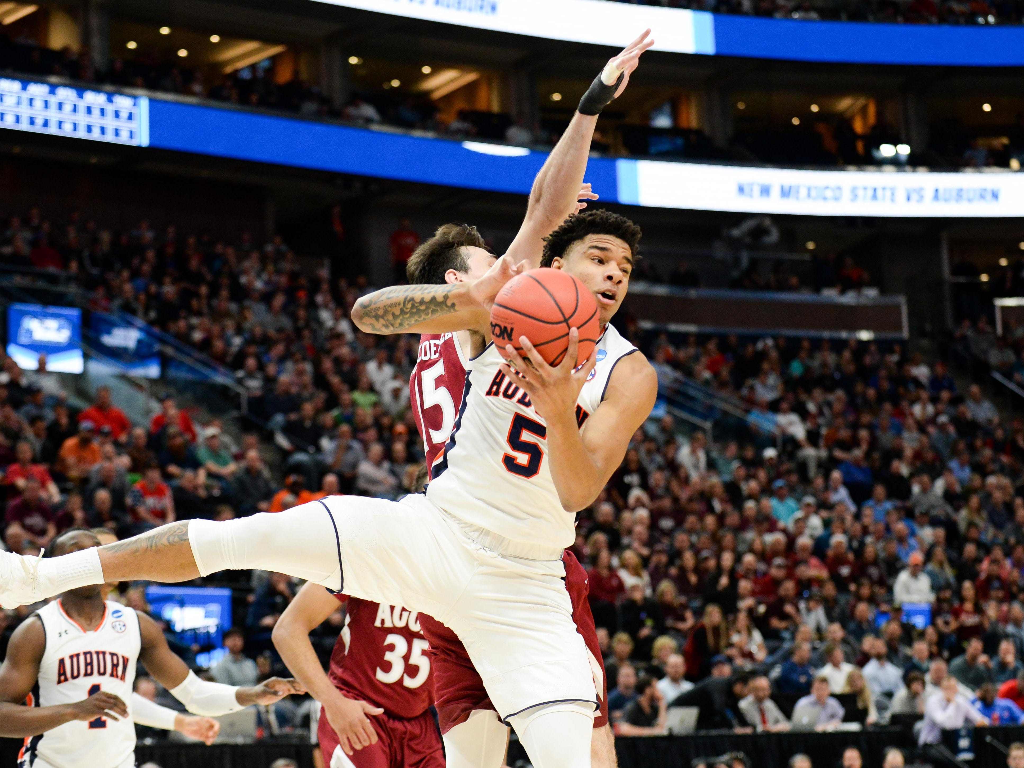 Auburn forward Chuma Okeke (5) brings down a rebound against New Mexico State forward Ivan Aurrecoechea (15) during the first round of the NCAA Tournament at Vivint Smart Home Arena on March 21, 2019, in Salt Lake City.