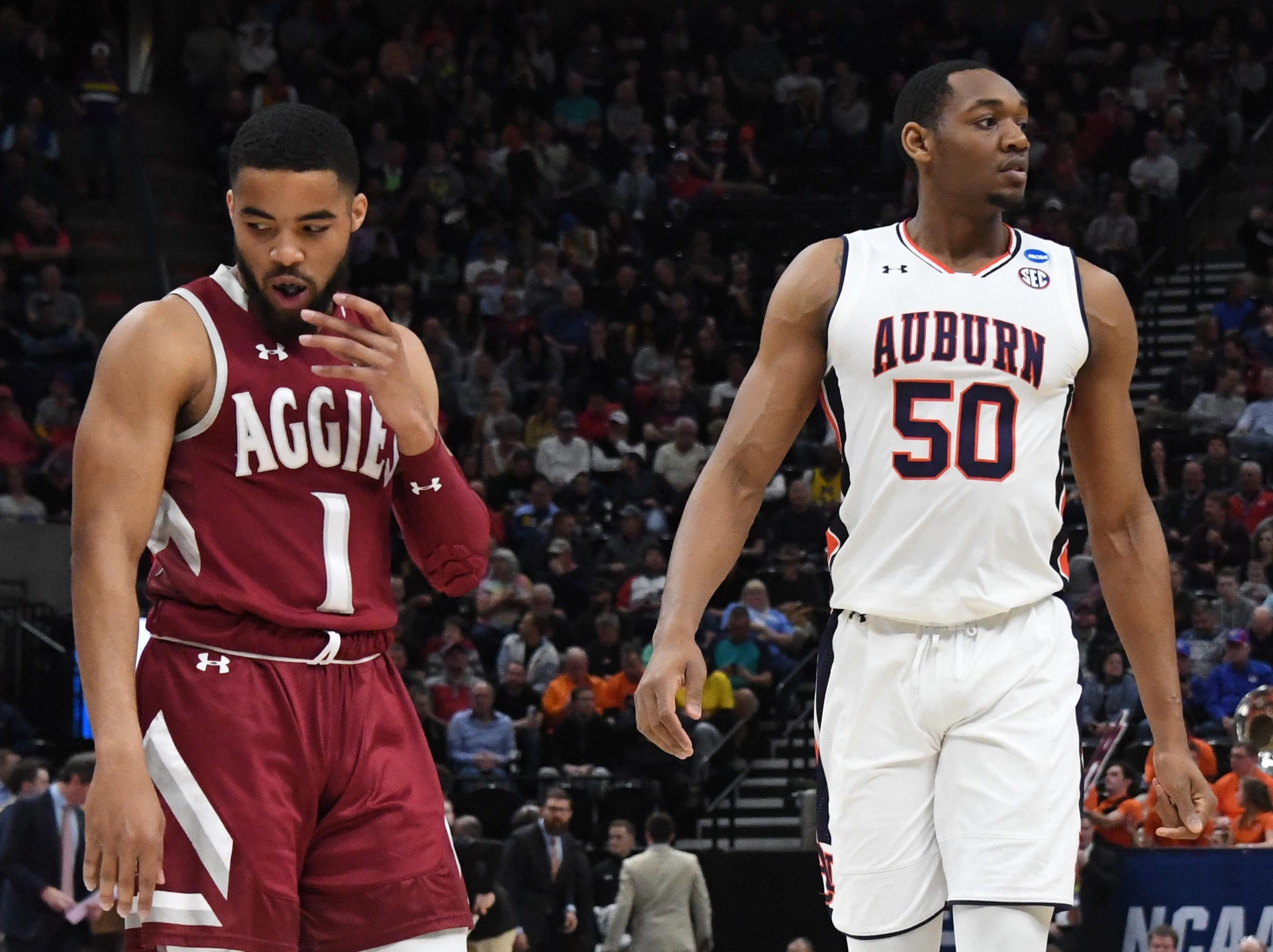 Mar 21, 2019; Salt Lake City, UT, USA; New Mexico State Aggies guard Shunn Buchanan (1) and Auburn Tigers center Austin Wiley (50) react during the first half in the first round of the 2019 NCAA Tournament at Vivint Smart Home Arena. Mandatory Credit: Kirby Lee-USA TODAY Sports