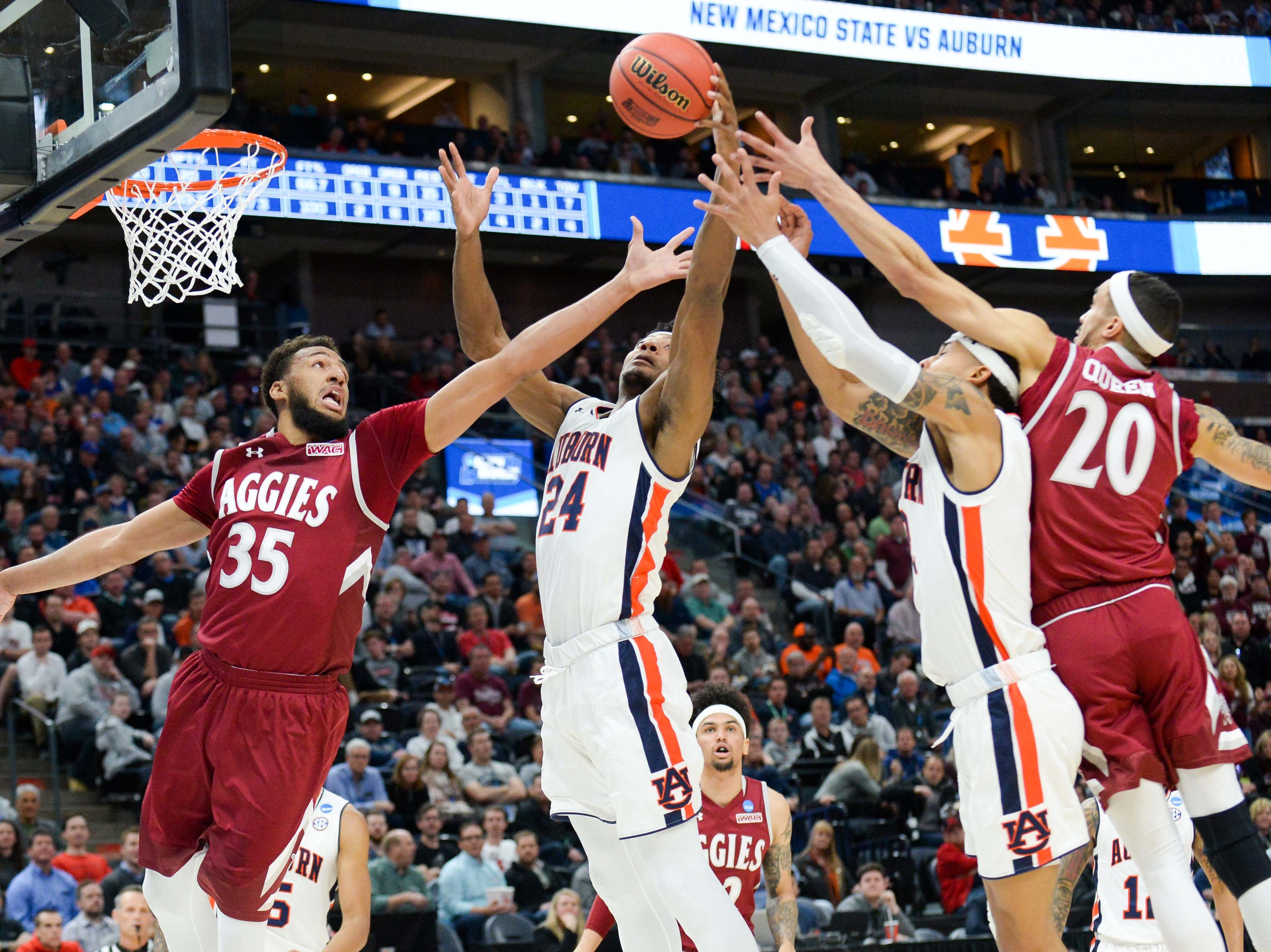 Mar 21, 2019; Salt Lake City, UT, USA; From left to right, New Mexico State Aggies forward Johnny McCants (35), Auburn Tigers forward Anfernee McLemore (24), guard Bryce Brown (2), and New Mexico State Aggies guard Trevelin Queen (20) reach for the ball during the first half in the first round of the 2019 NCAA Tournament at Vivint Smart Home Arena. Mandatory Credit: Gary A. Vasquez-USA TODAY Sports