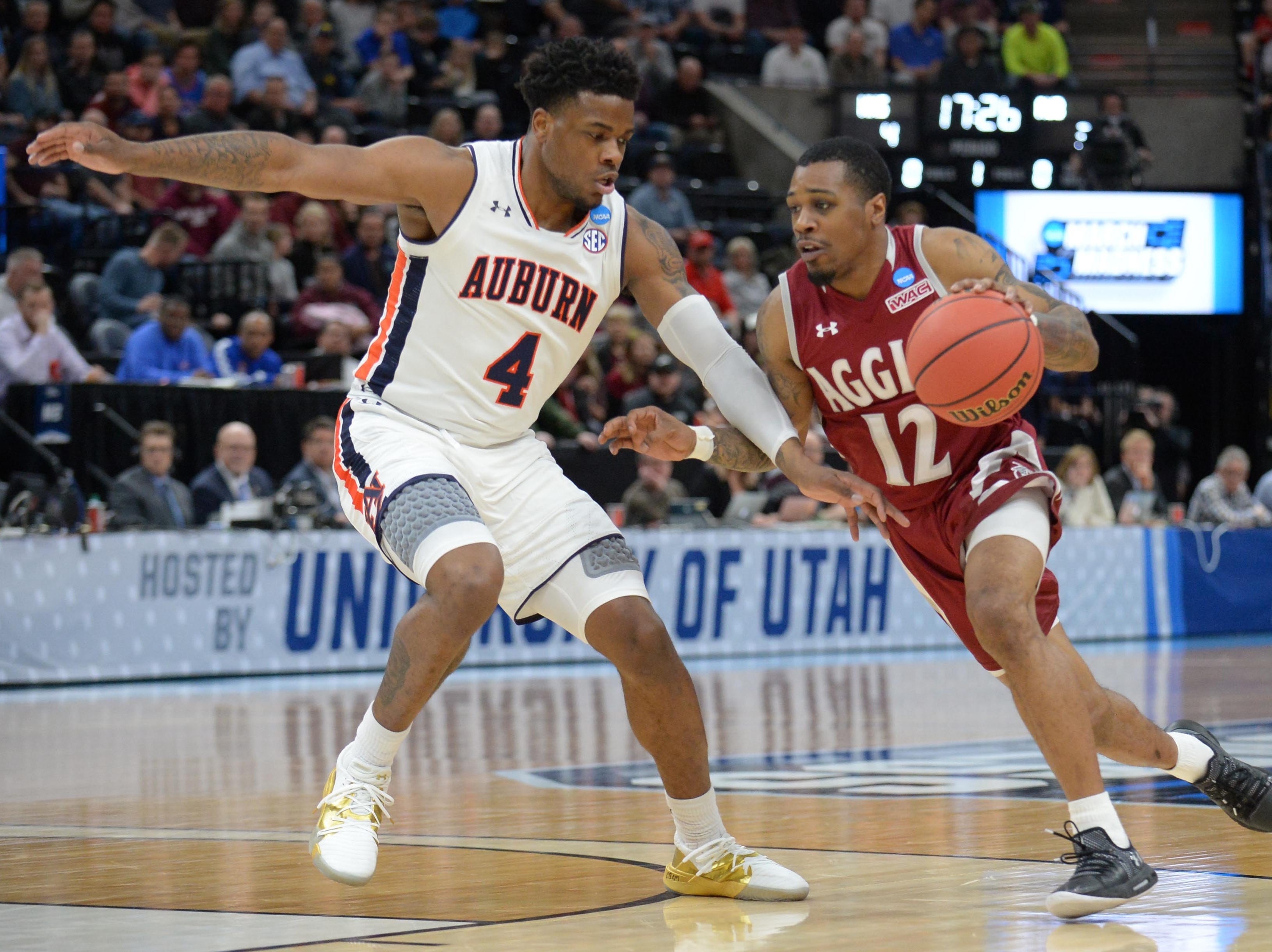 Mar 21, 2019; Salt Lake City, UT, USA; Auburn Tigers guard Malik Dunbar (4) defends New Mexico State Aggies guard AJ Harris (12) during the first half in the first round of the 2019 NCAA Tournament at Vivint Smart Home Arena. Mandatory Credit: Gary A. Vasquez-USA TODAY Sports