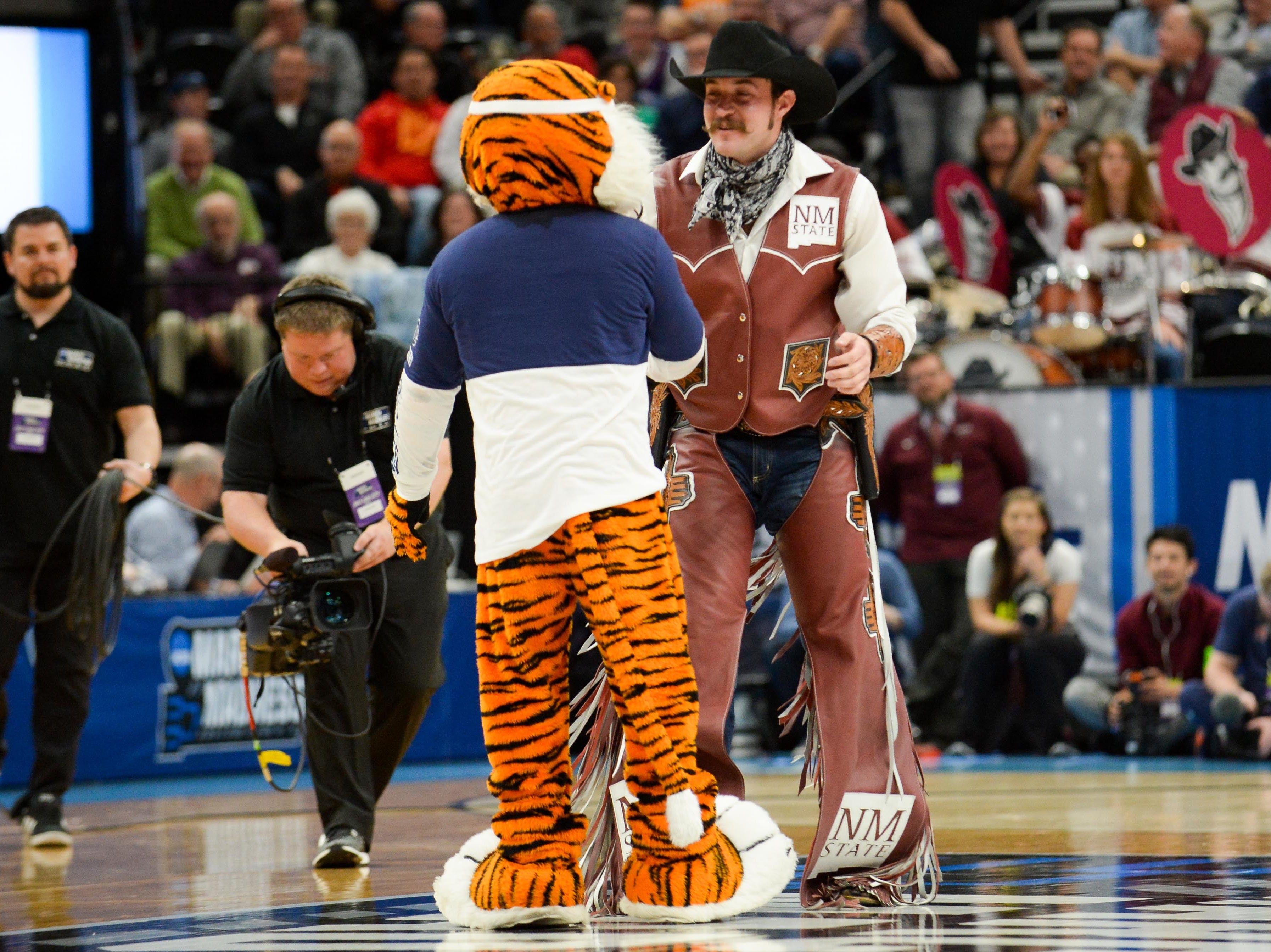 Mar 21, 2019; Salt Lake City, UT, USA; The mascots for Auburn Tigers and New Mexico State Aggies meet on the court during the first half in the first round of the 2019 NCAA Tournament at Vivint Smart Home Arena. Mandatory Credit: Gary A. Vasquez-USA TODAY Sports