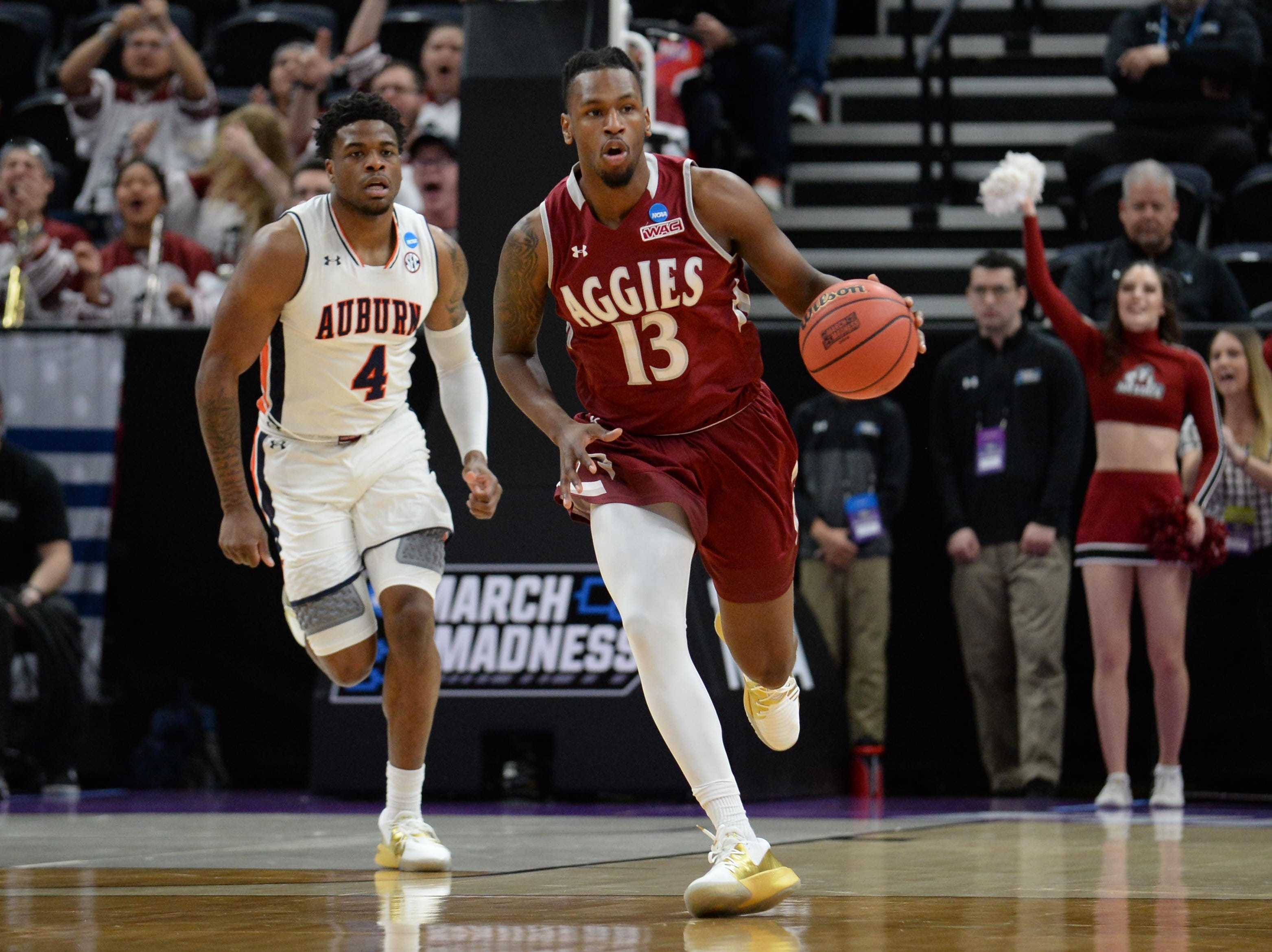Mar 21, 2019; Salt Lake City, UT, USA; New Mexico State Aggies forward C.J. Bobbitt (13) brings the ball up court as Auburn Tigers guard Malik Dunbar (4) trails during the first half in the first round of the 2019 NCAA Tournament at Vivint Smart Home Arena. Mandatory Credit: Gary A. Vasquez-USA TODAY Sports
