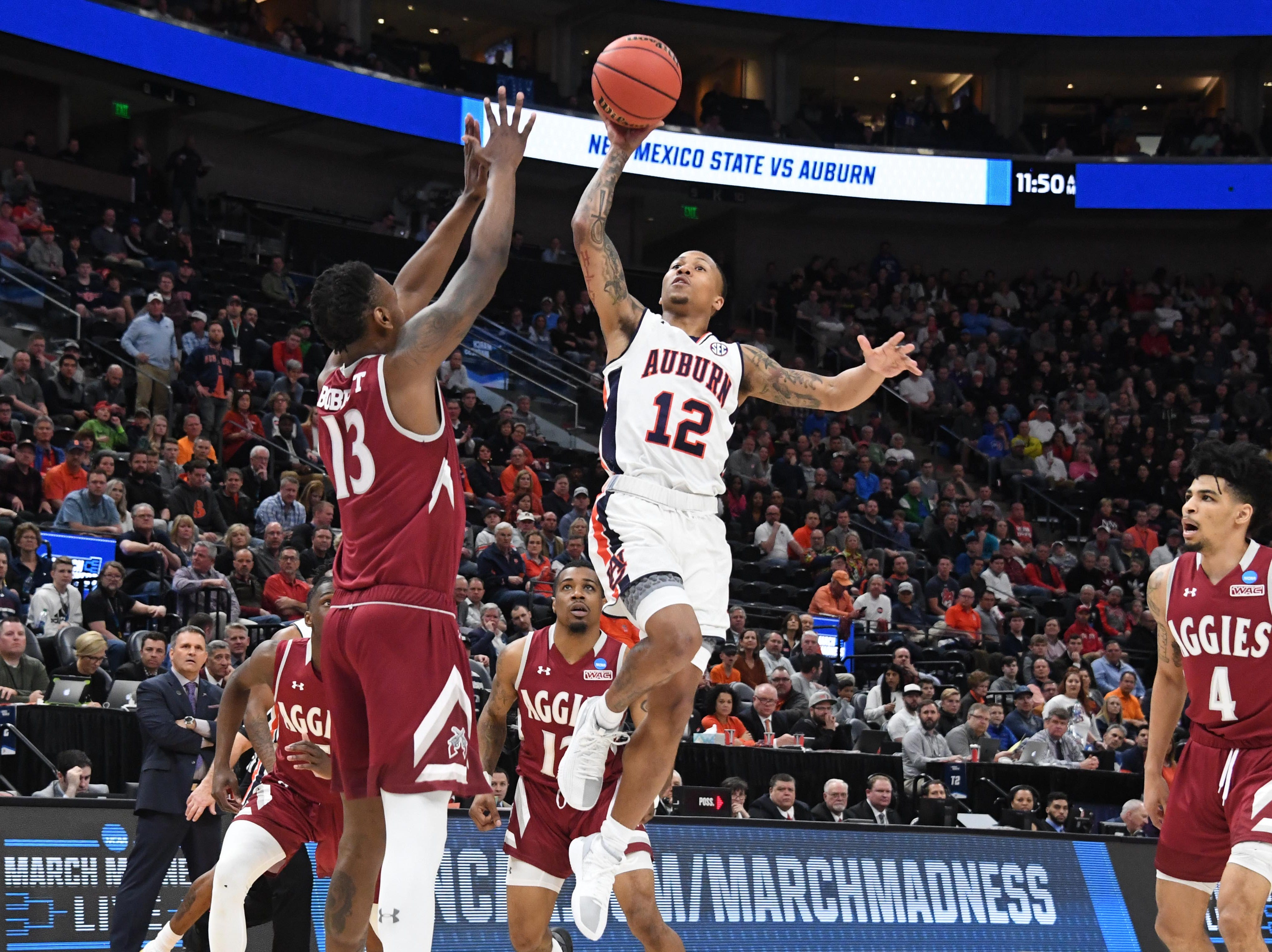 Mar 21, 2019; Salt Lake City, UT, USA; Auburn Tigers guard J'Von McCormick (12) shoots as New Mexico State Aggies forward C.J. Bobbitt (13) defends during the first half in the first round of the 2019 NCAA Tournament at Vivint Smart Home Arena. Mandatory Credit: Kirby Lee-USA TODAY Sports
