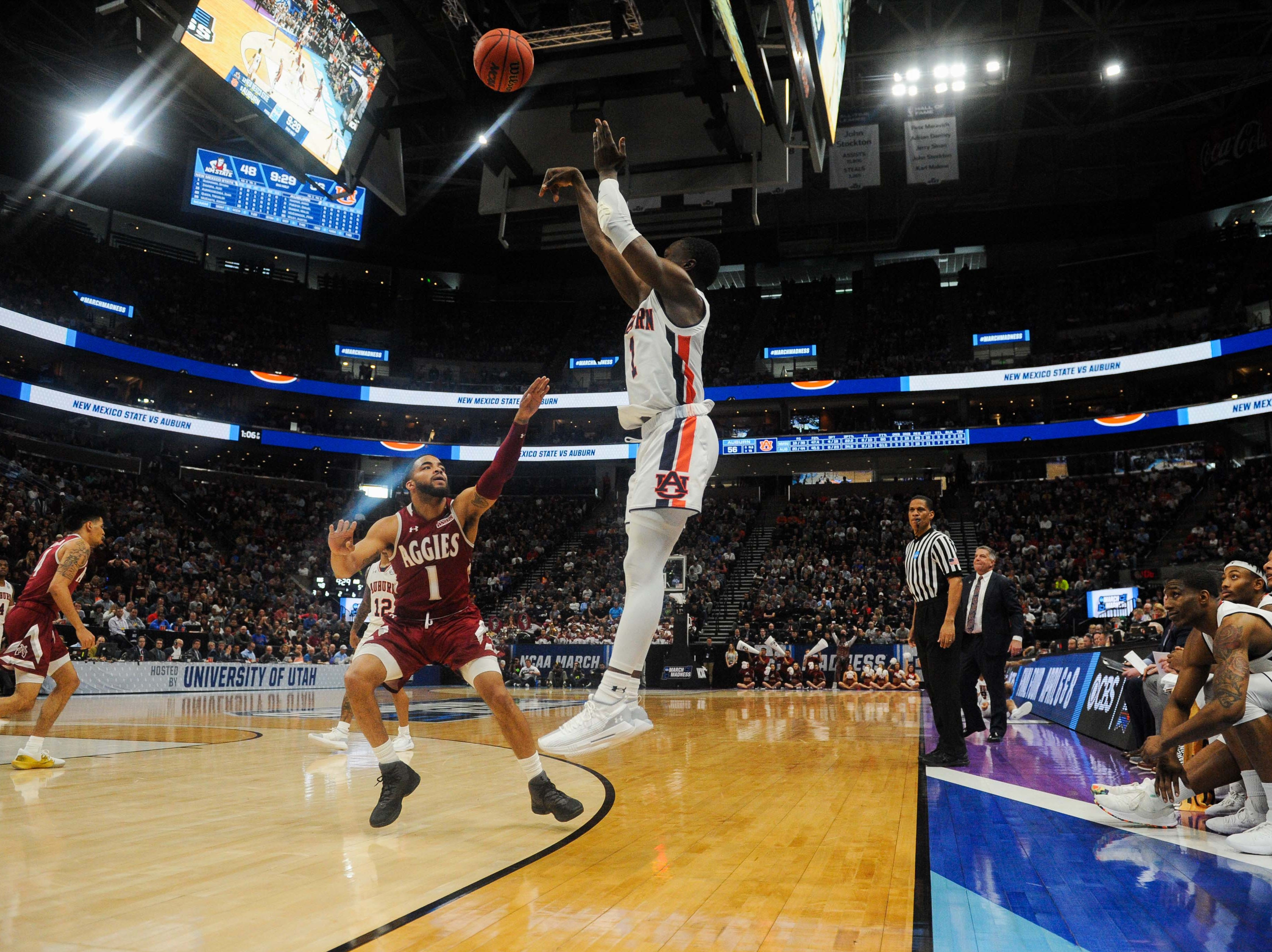 Mar 21, 2019; Salt Lake City, UT, USA; Auburn Tigers guard Jared Harper (1) shoots a three-pointer over New Mexico State Aggies guard Shunn Buchanan (1) during the second half in the first round of the 2019 NCAA Tournament at Vivint Smart Home Arena. Mandatory Credit: Gary A. Vasquez-USA TODAY Sports