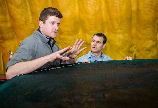 Sen. Todd Young listens to Peter Bowyer during a tour of the AquaBounty salmon farm in Albany.