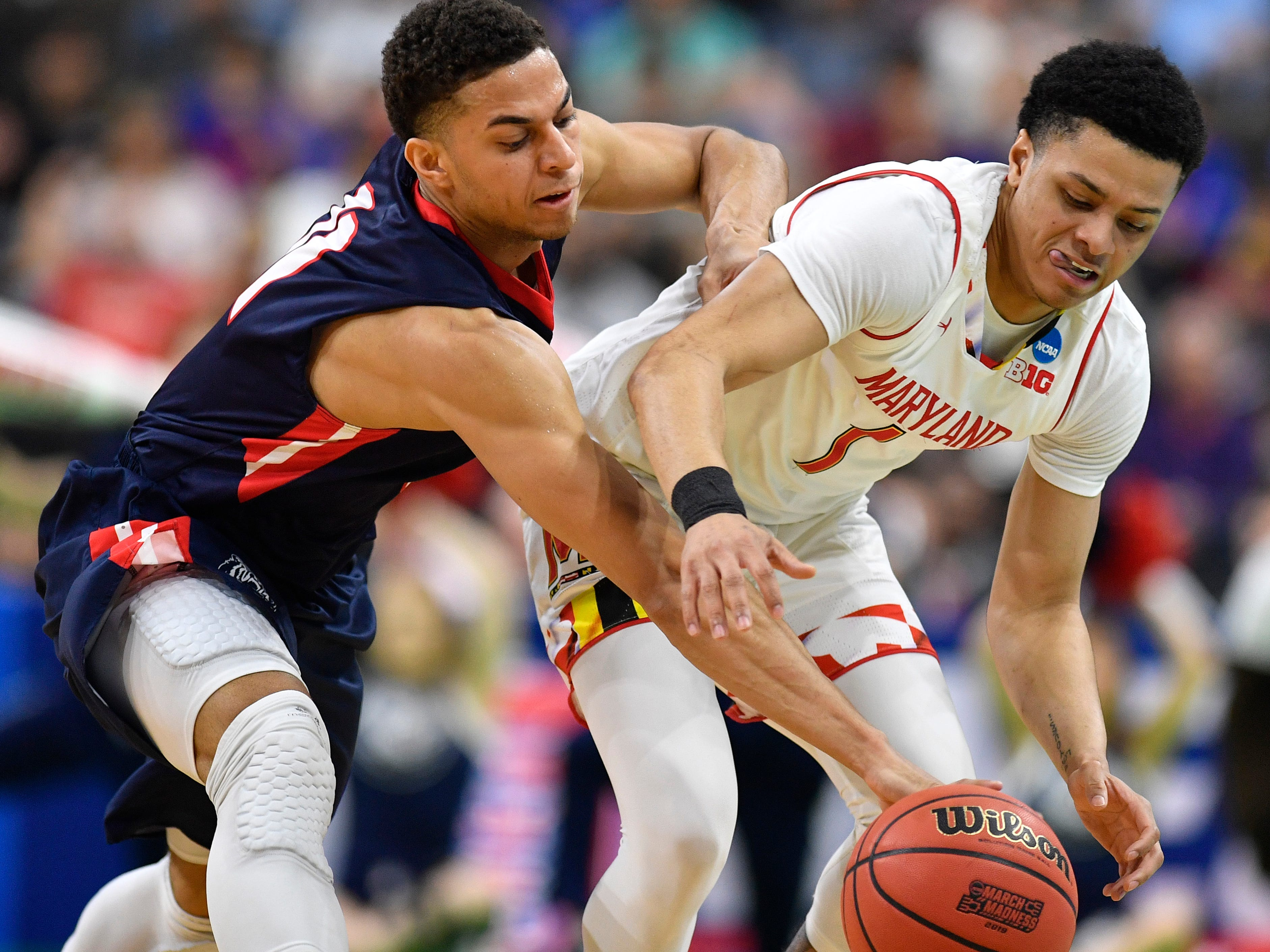 Belmont guard Kevin McClain (11) and Maryland guard Anthony Cowan Jr. (1) chase after a ball during the first half of the first-round NCAA college basketball tournament game at VyStar Veterans Memorial Arena in Jacksonville, Fla., Thursday, March 21, 2019.