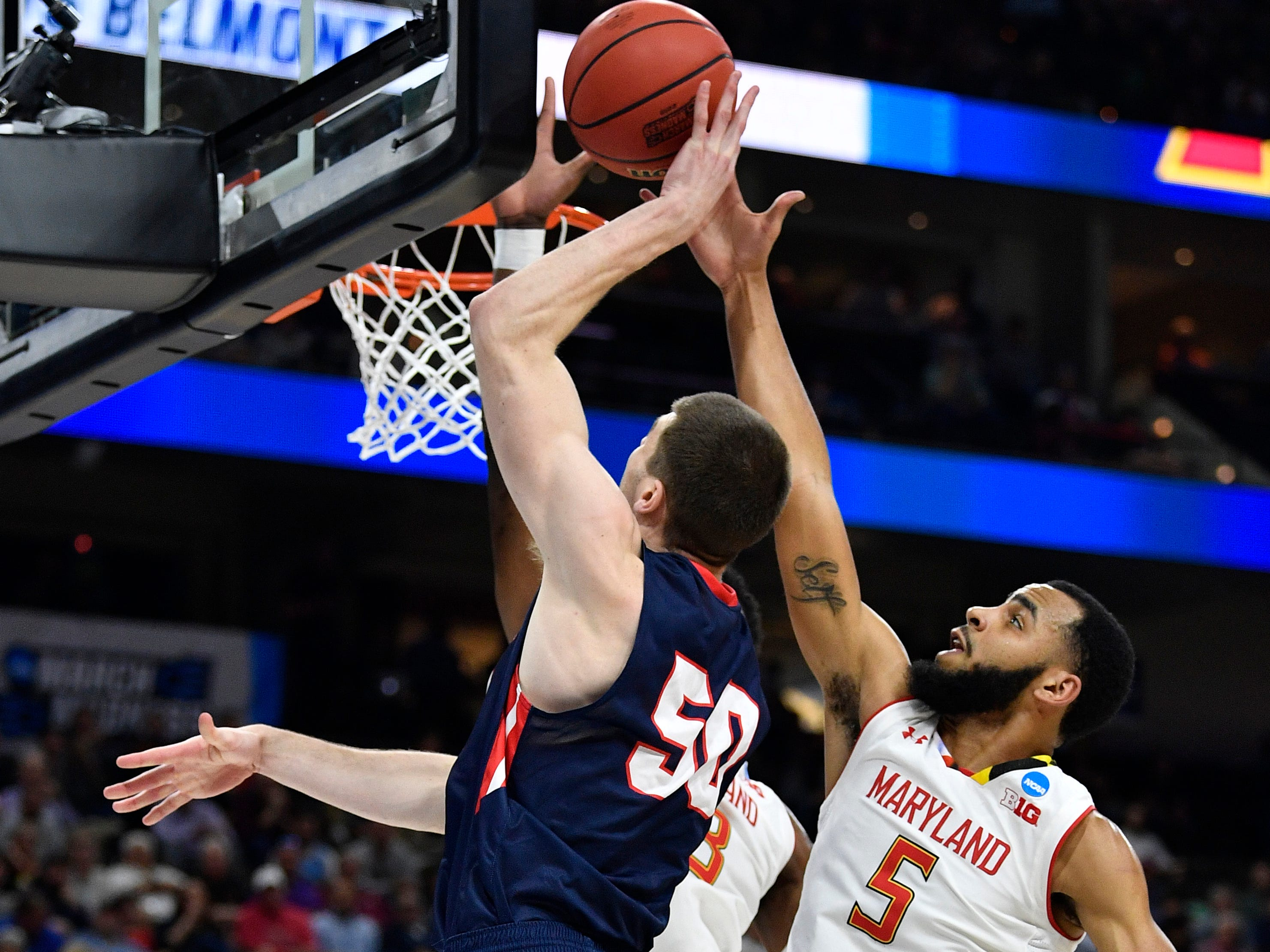 Belmont center Seth Adelsperger (50) tries to shoot past Maryland guard Eric Ayala (5) during the first half of the first-round NCAA college basketball tournament game at VyStar Veterans Memorial Arena in Jacksonville, Fla., Thursday, March 21, 2019.