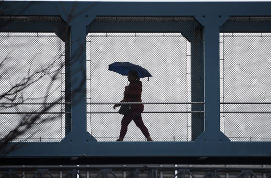 A woman with an umbrella walks across an overpass on Route 4 in Paramus on 03/20119.