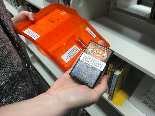 """Bergenfield Library Director Allison Moonitz is holding a portable, self-playing digital audio bookknown as """"Playaway."""""""