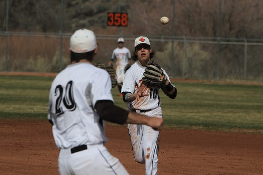 Aztec's Derek Jung flips the ball to Chad Hill at first base for an out against Bayfield during Thursday's game at AHS.