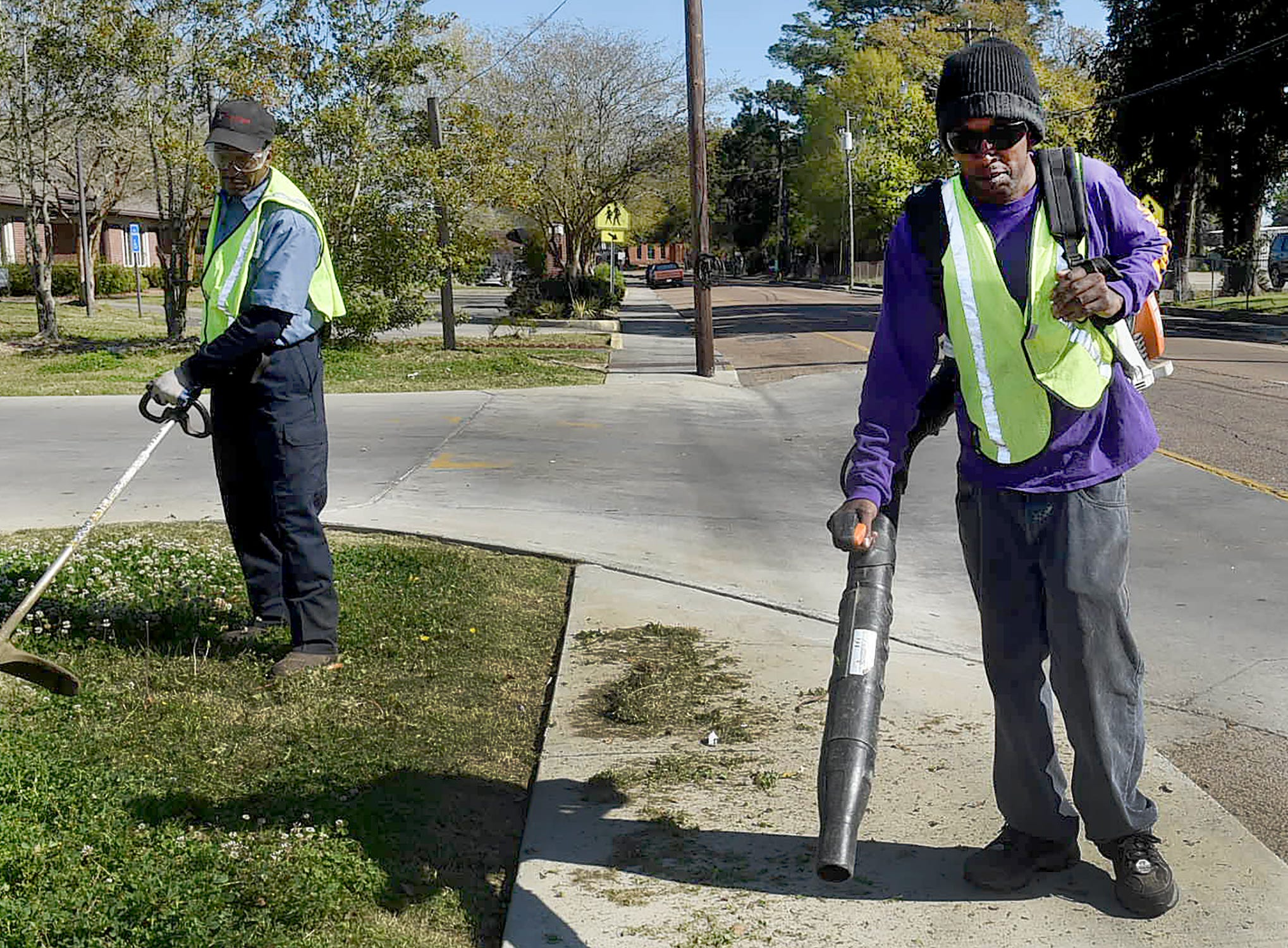 City of Opelousas employees Adam Coleman, left, and Charles Roberts spruce up the roadside around Holy Ghost Catholic Church Thursday morning in anticipation of the upcoming Louisiana Cleanest City Contest.
