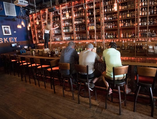 "Bartender Savanna Ferrer retrieves a favorite whiskey from the wall at the Old Hickory Whiskey Bar in downtown Pensacola on March 20, 2019.  Old Hickory and Flora-Bama are two Pensacola bars in Garden & Gun's Magazine's ""Southern Bar Bracket,"" which pits 32 of the best bars in the south against each other in a March-Madness-style tournament determined by a series of reader polls."