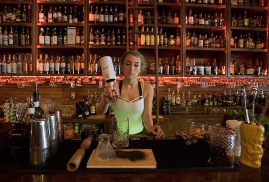 """Bartender Savanna Ferrer mixes up a signature drink at the Old Hickory Whiskey Bar in downtown Pensacola on Wednesday, March 20, 2019. Old Hickory and Flora-Bama are two Pensacola bars in Garden & Gun's Magazine's """"Southern Bar Bracket,"""" which pits 32 of the best bars in the south against each other in a March-Madness-style tournament determined by a series of reader polls."""