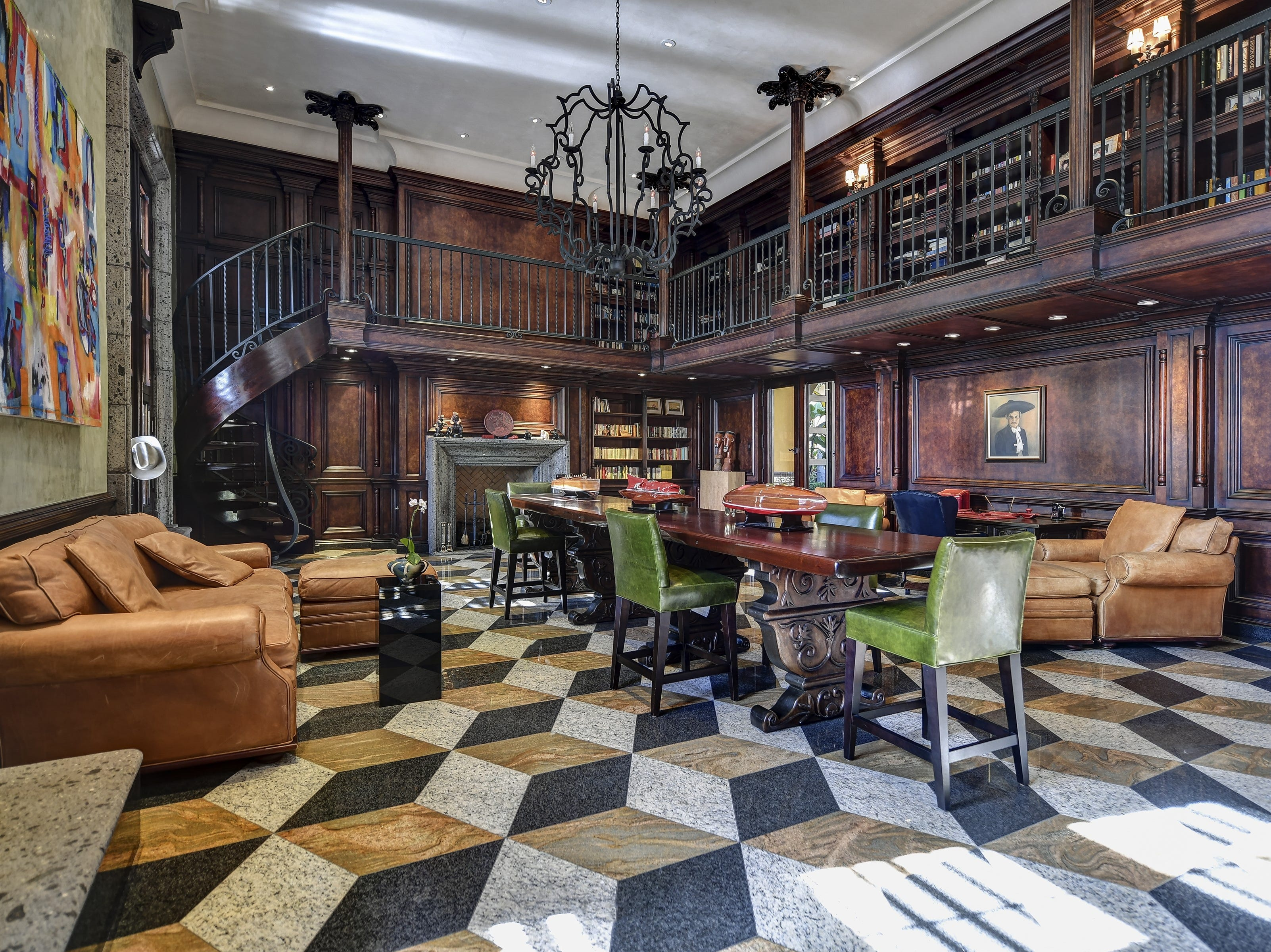 The custom wood-paneled library of the PV mansion, purchased by Amy Connor, features a custom iron spiral staircase that leads to the upper bookcase.