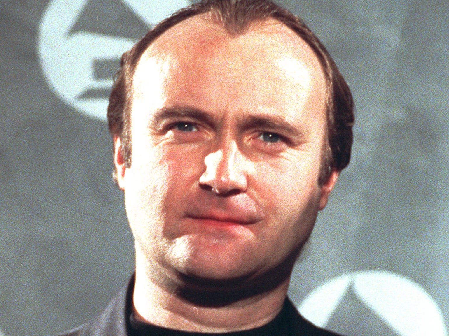 Phil Collins holds his Grammy award in a 1991 file photo.