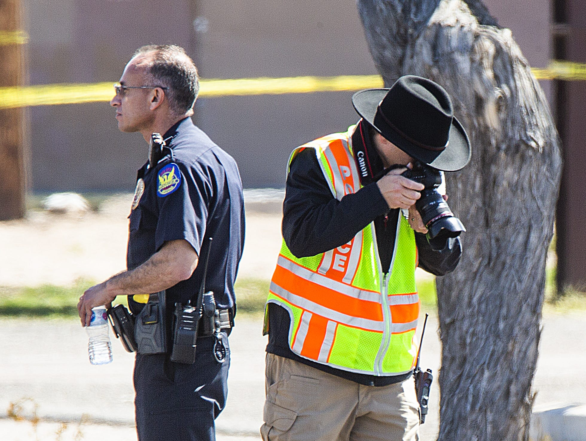 A police photographer takes photos the scene at Indian School Road near 75th Avenue in Phoenix where a police officer was hit while investigating a crash on March 21, 2019.