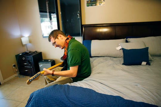 Alex Goldstein plays guitar in his room in Tempe, Ariz. on March 10, 2019. Goldstein has schizophrenia and cycled between the streets and treatment programs and now is settled into a group home run by a nonprofit, Marc Community Resources.