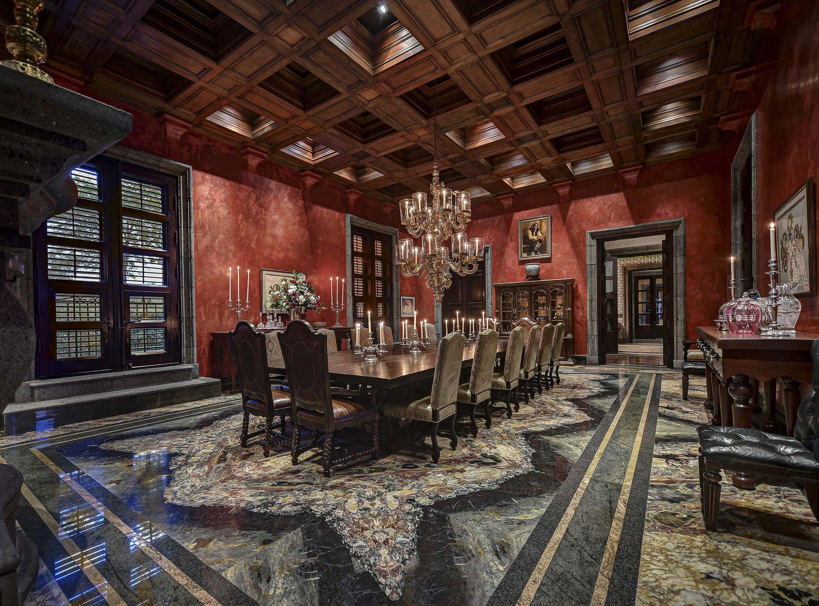 The Paradise Valley estate, sold by Christopher Leclair Daugherty, includes a luxurious formal dining room with 18-foot coffered ceilings and candle chandeliers.