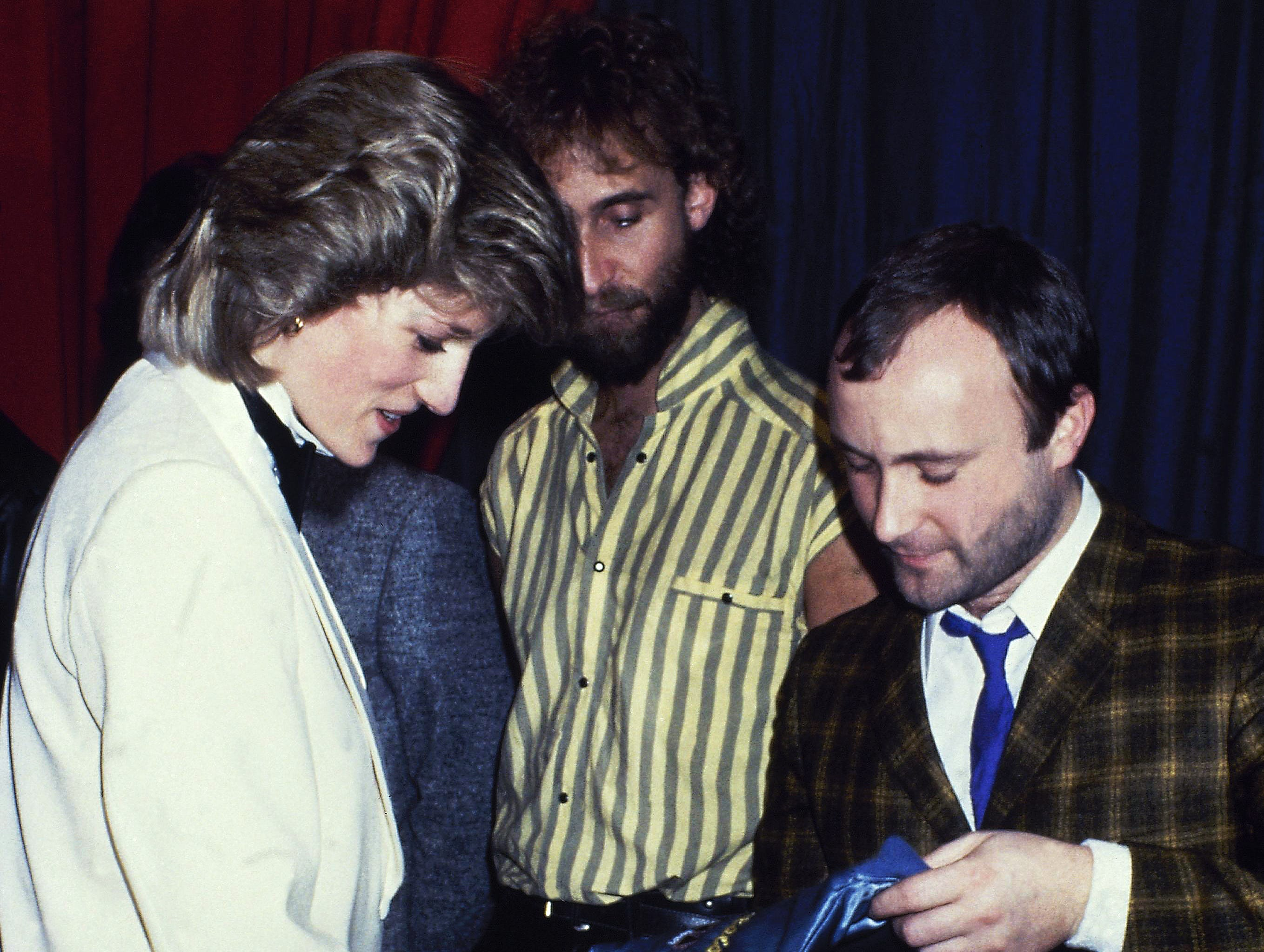 Britain's Princess Diana talks with rock group Genesis with Mike Rutherford, and Phil Collins in February 1984. The princess surprised her fashion fans when she stepped out in a white dinner jacket, black trousers and silk, black bow tie to see the band Genesis perform a charity gig.