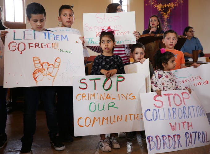 Children hold signs during a press conference on March 20, 2019, at Southside Presbyterian Church, 317 W. 23rd St., in Tucson. A family of three was arrested after a traffic stop by a state trooper where Border Patrol was called to assist.