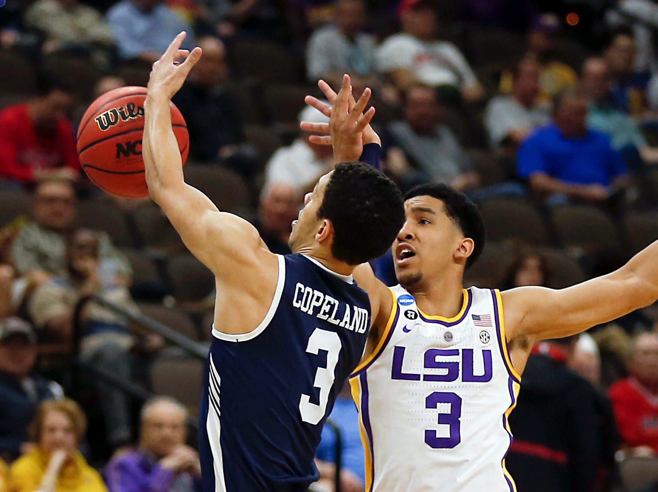 Yale 's Alex Copeland, left, and LSU's Tremont Waters go after a loose ball during the first half of a first round men's college basketball game in the NCAA Tournament, in Jacksonville, Fla. Thursday, March 21, 2019. (AP Photo/Stephen B. Morton)