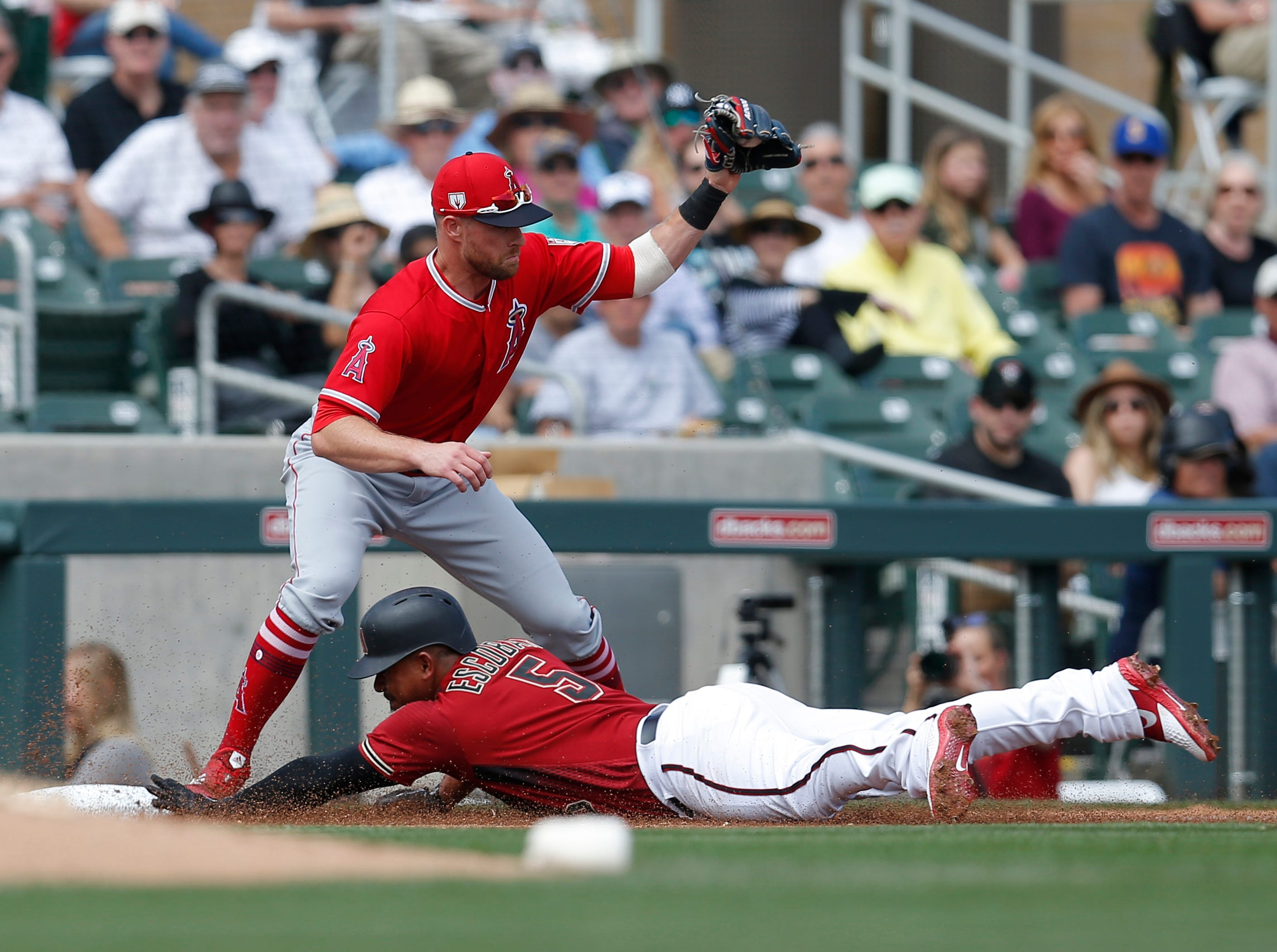 Diamondbacks third baseman Eduardo Escobar (5) sides into third base on a triple during the first inning of a spring training game against the Los Angeles Angels at Salt River Fields.