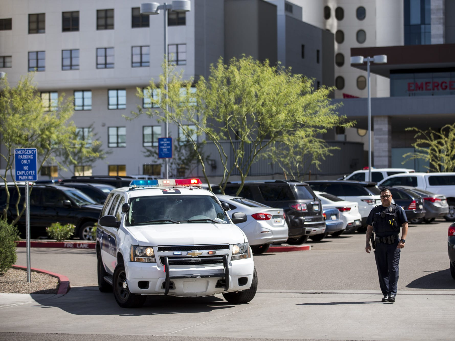 A Phoenix police officer stands guard outside Banner University Medical Center on March 21, 2019, in Phoenix. A 23-year Phoenix police veteran was killed after being struck during a crash investigation near 75th Avenue and Indian School Road.