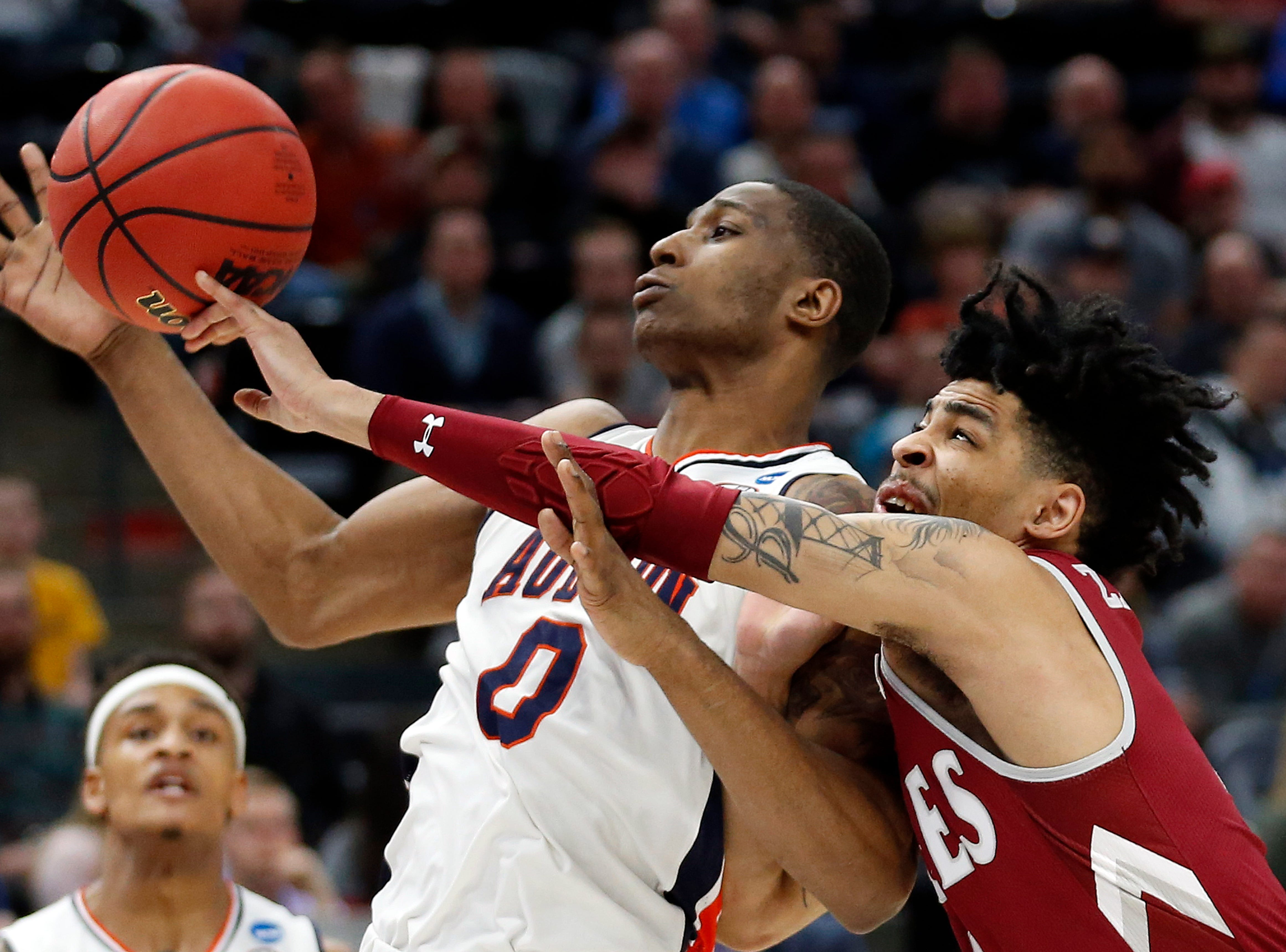 Auburn's forward Horace Spencer (0) and New Mexico State guard JoJo Zamora (4) battle for a rebound in the first half during a first round men's college basketball game in the NCAA Tournament, Thursday, March 21, 2019, in Salt Lake City. (AP Photo/Rick Bowmer)