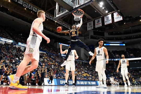 Murray State's Ja Morant (12) dunks on Marquette during a first-round game of the NCAA Tournament.