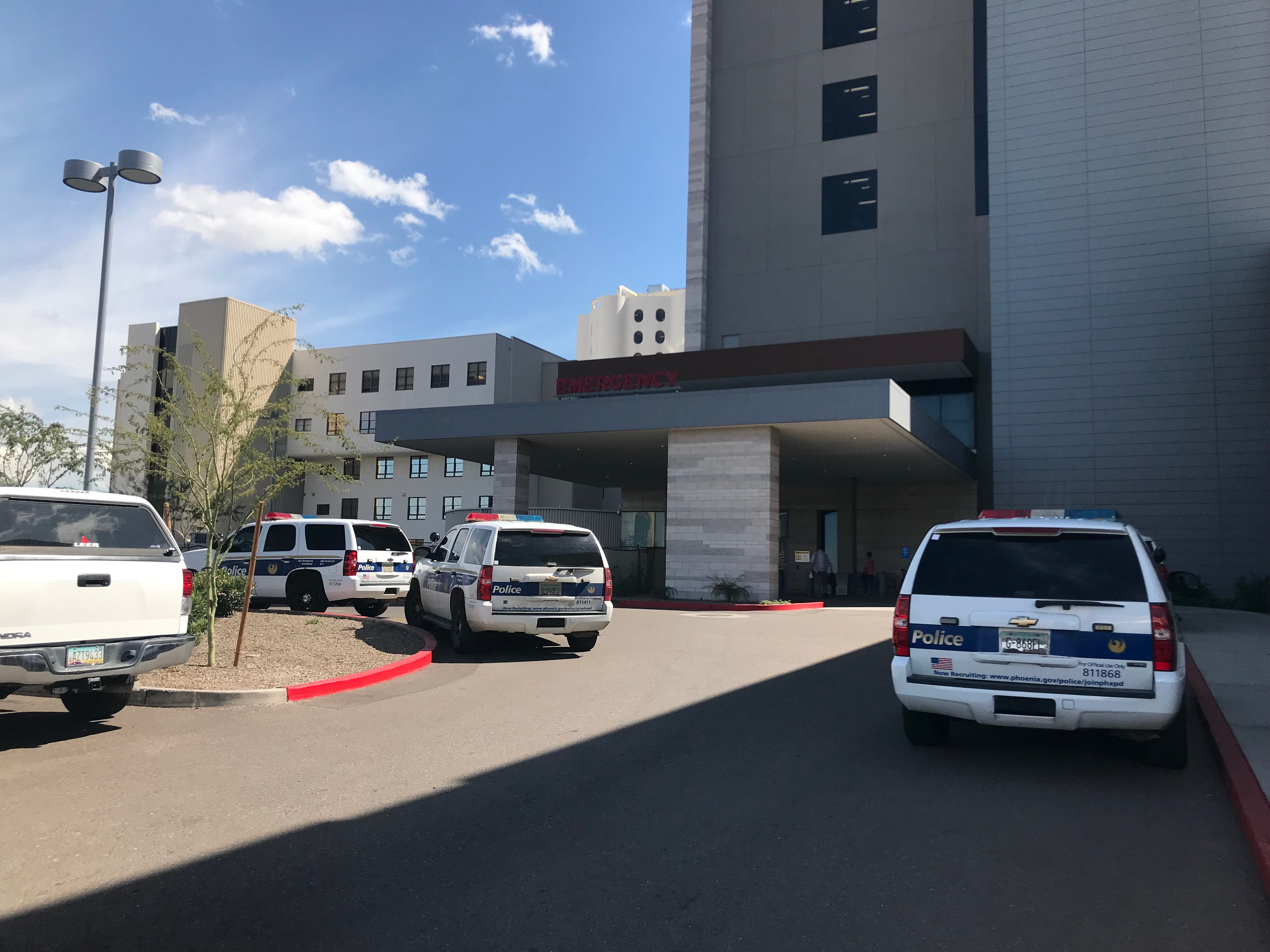 Phoenix police officers gather at Banner University Medical Center after Officer Paul Rutherford, 51, died Thursday after being struck by a vehicle while officers were investigating a collision at 75th Avenue and Indian School Road.