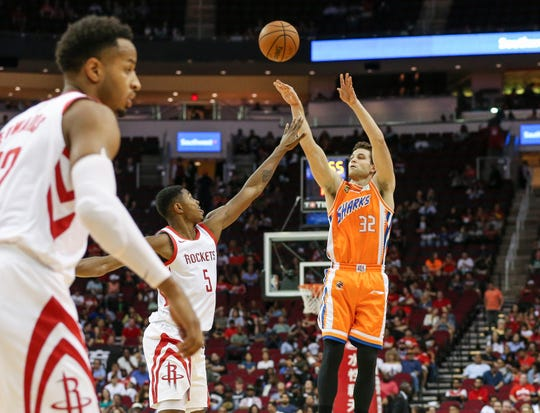 Shanghai Sharks guard Jimmer Fredette (32) shoots the ball over Houston Rockets forward Bruno Caboclo (5) during the third quarter at Toyota Center in the 2018 NBA preseason.