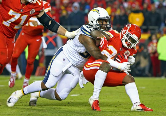 Kansas City Chiefs running back Damien Williams (26) is tackled by Los Angeles Chargers defensive end Darius Philon (93) in the second half at Arrowhead Stadium in a game last season.