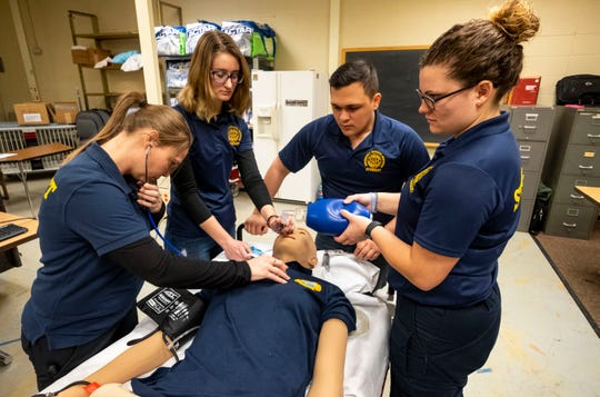 Amanda Aldridge, left, checks blood pressure on a training mannequin while Audrey Sylvia, second from left, Jerson Arauz, second from right, and Tori Fite ventilate after intubating the mannequin during a drill Thursday, March 21, 2019 at SC4.