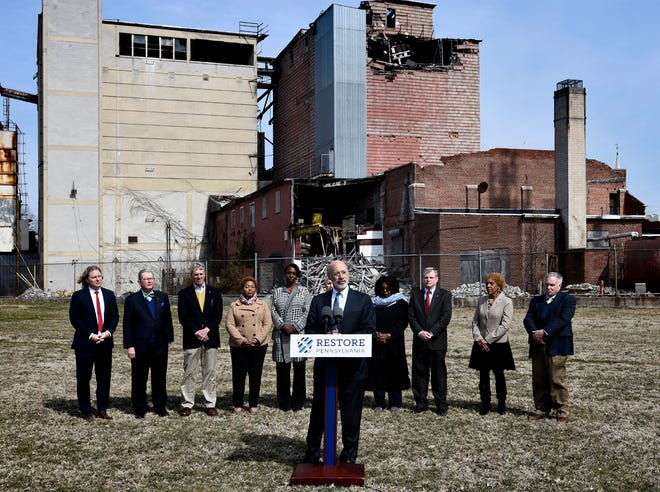 "Gov. Tom Wolf speaks Wednesday, March 20, 2019, at the York Fairgrounds as part of his tour across the commonwealth to stump for ""Restore Pennsylvania,"" a $4.5 billion infrastructure plan. He appeared with the abandoned Manna Pro Corporation grain elevator as a backdrop. A local delegation, background, joined him for the press conference. Bill Kalina photo"