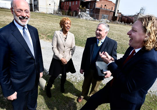 """Pennsylvania Gov. Tom Wolf meets with, from left, state Rep. Carol Hill-Evans, York County Vice President Commissioner Doug Hoke and York County Economic Alliance CEO Kevin Schreiber before speaking Wednesday, March 20, 2019. Wolf appeared at the York Fairgrounds, with a backdrop of the abandoned Manna Pro Corporation grain elevator (background), as part of his tour across the commonwealth to stump for """"Restore Pennsylvania,"""" a $4.5 billion infrastructure plan. Bill Kalina photo"""