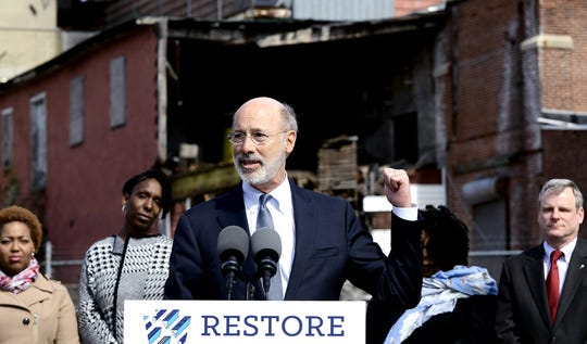 """Gov. Tom Wolf gestures toward the the abandoned Manna Pro Corporation grain elevator while speaking Wednesday, March 20, 2019. Wolf appeared at the York Fairgrounds as part of his tour across the commonwealth to stump for """"Restore Pennsylvania,"""" a $4.5 billion infrastructure plan. A local delegation, background, joined him for the press conference. Bill Kalina photo"""
