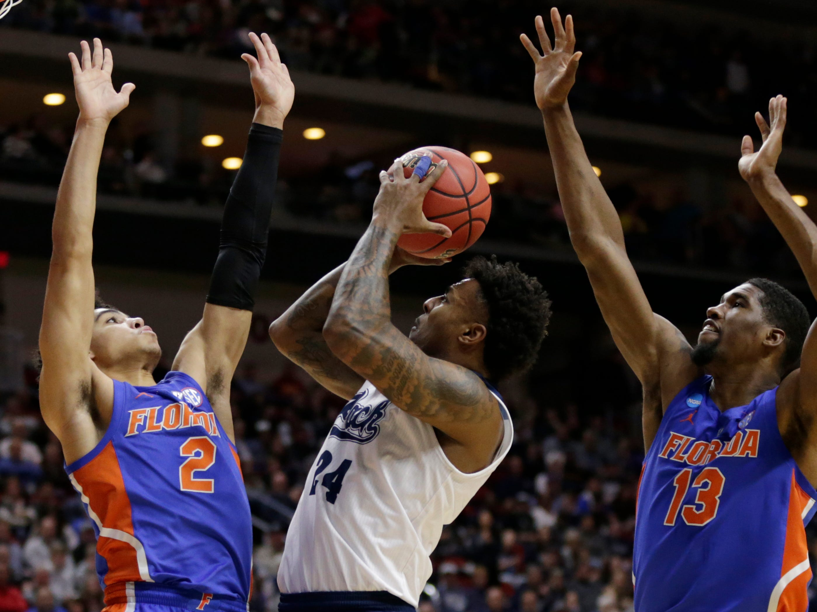 Nevada's Jordan Caroline (24) shoots between Florida's Andrew Nembhard (2) and Kevarrius Hayes (13) during the first half of a first round men's college basketball game in the NCAA Tournament in Des Moines, Iowa, Thursday, March 21, 2019. (AP Photo/Nati Harnik)